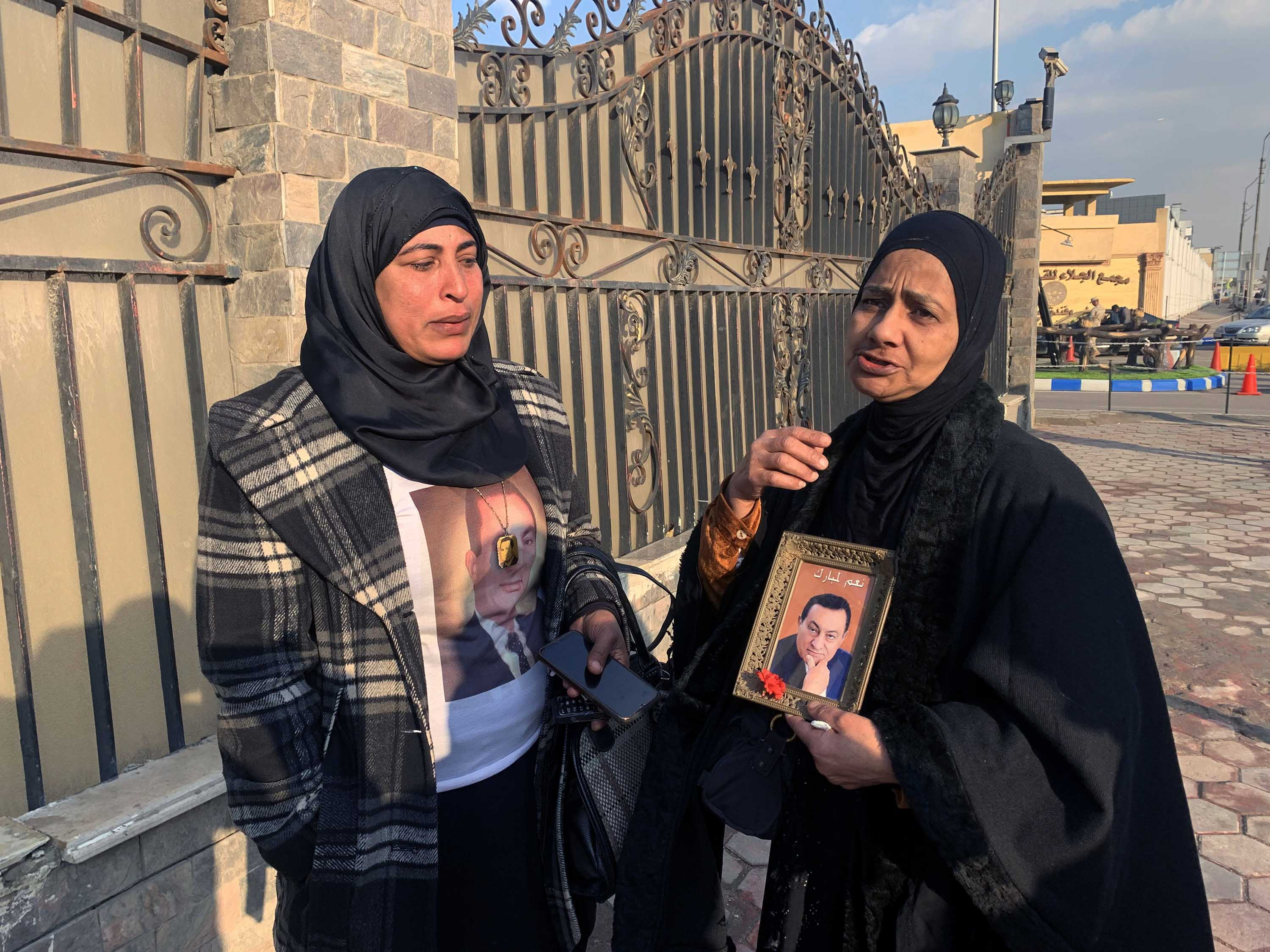 Supporters of former president Hosni Mubarak hold pictures of him outside a military hospital in Cairo on Tuesday, following the news of his death.