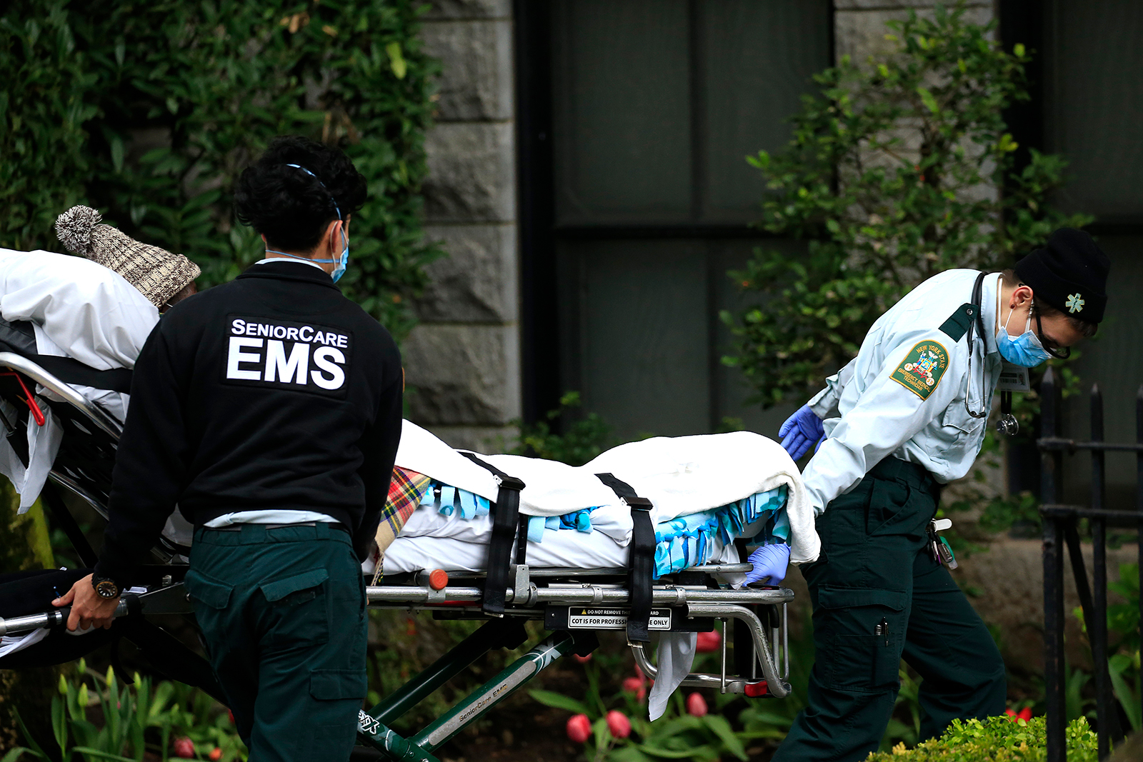 Emergency Medical Service workers unload a patient out of their ambulance at the Cobble Hill Health Center on April 18, in the Cobble Hill neighborhood of the Brooklyn borough of New York City. The nursing home has had at least 55 COVID-19 reported deaths.
