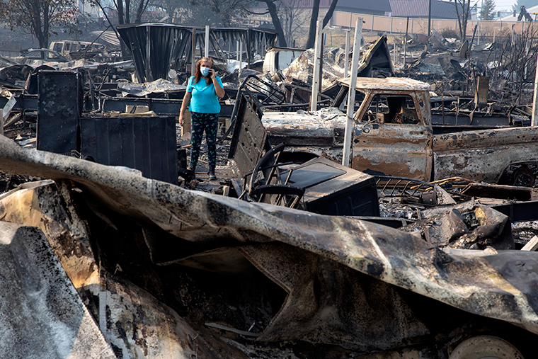 Heather Marshall talks to her mother as she stands by the ruins of her home at Coleman Creek Estates mobile home park in Phoenix, Oregon, Thursday, September 10, after a wildfire swept through. The Marshalls lived at the park for 21 years.