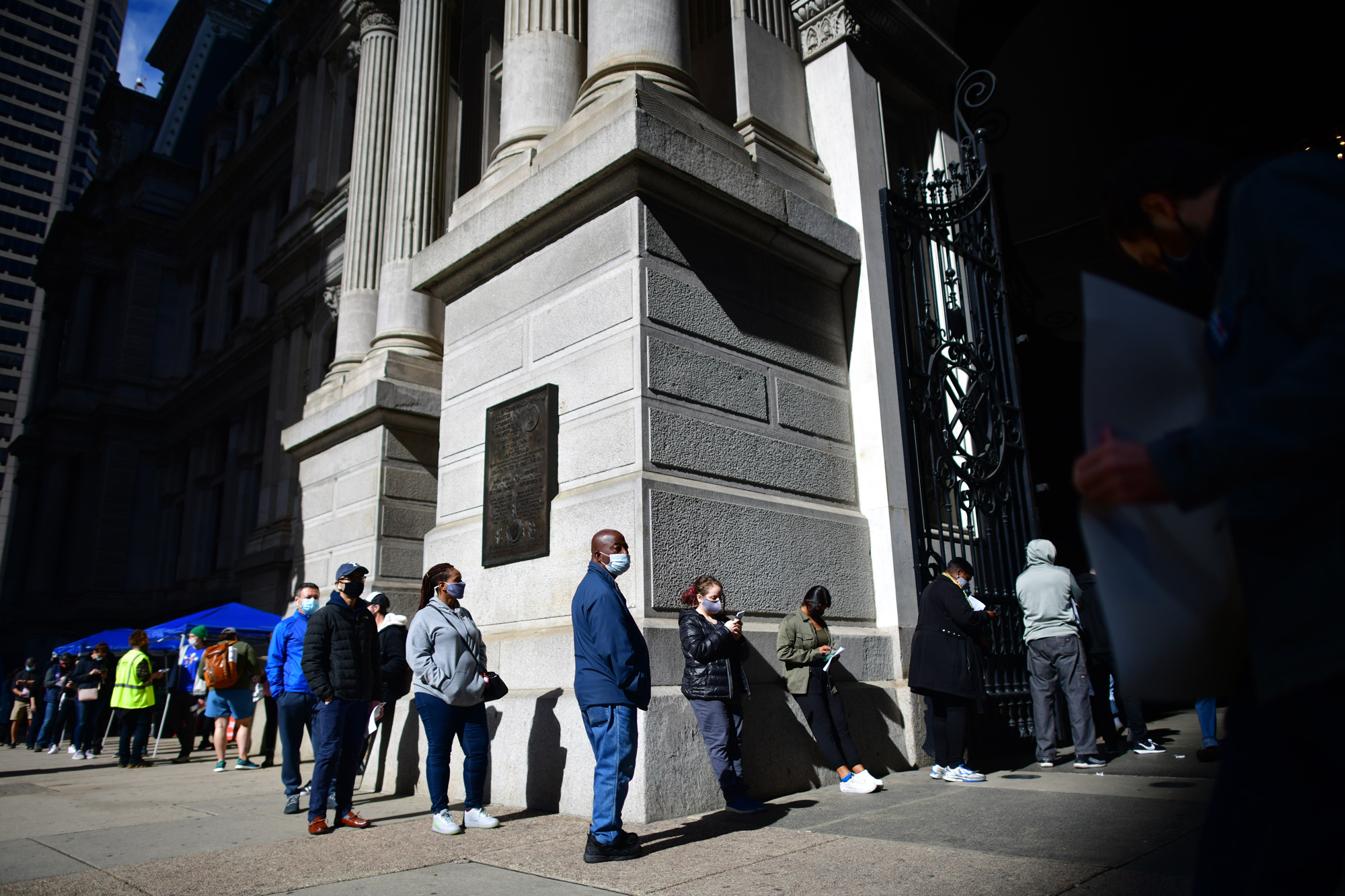 Voters wait in line outside Philadelphia City Hall to cast their early voting ballots at the satellite polling station on October 27 in Philadelphia, Pennsylvania.