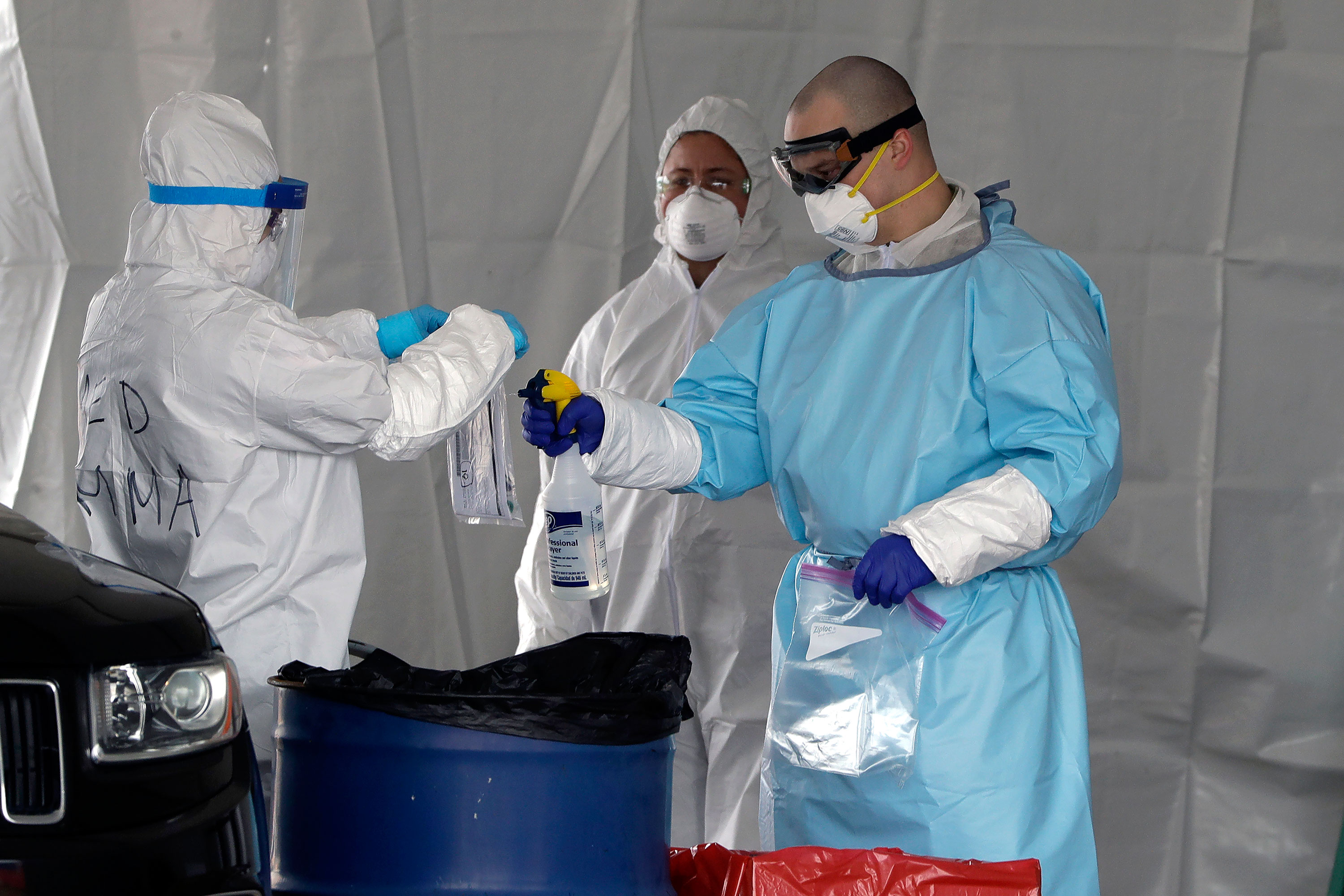 Medical workers spray a bag containing a coronavirus test at a drive-through testing site in Foxborough, Massachusetts, on April 5.