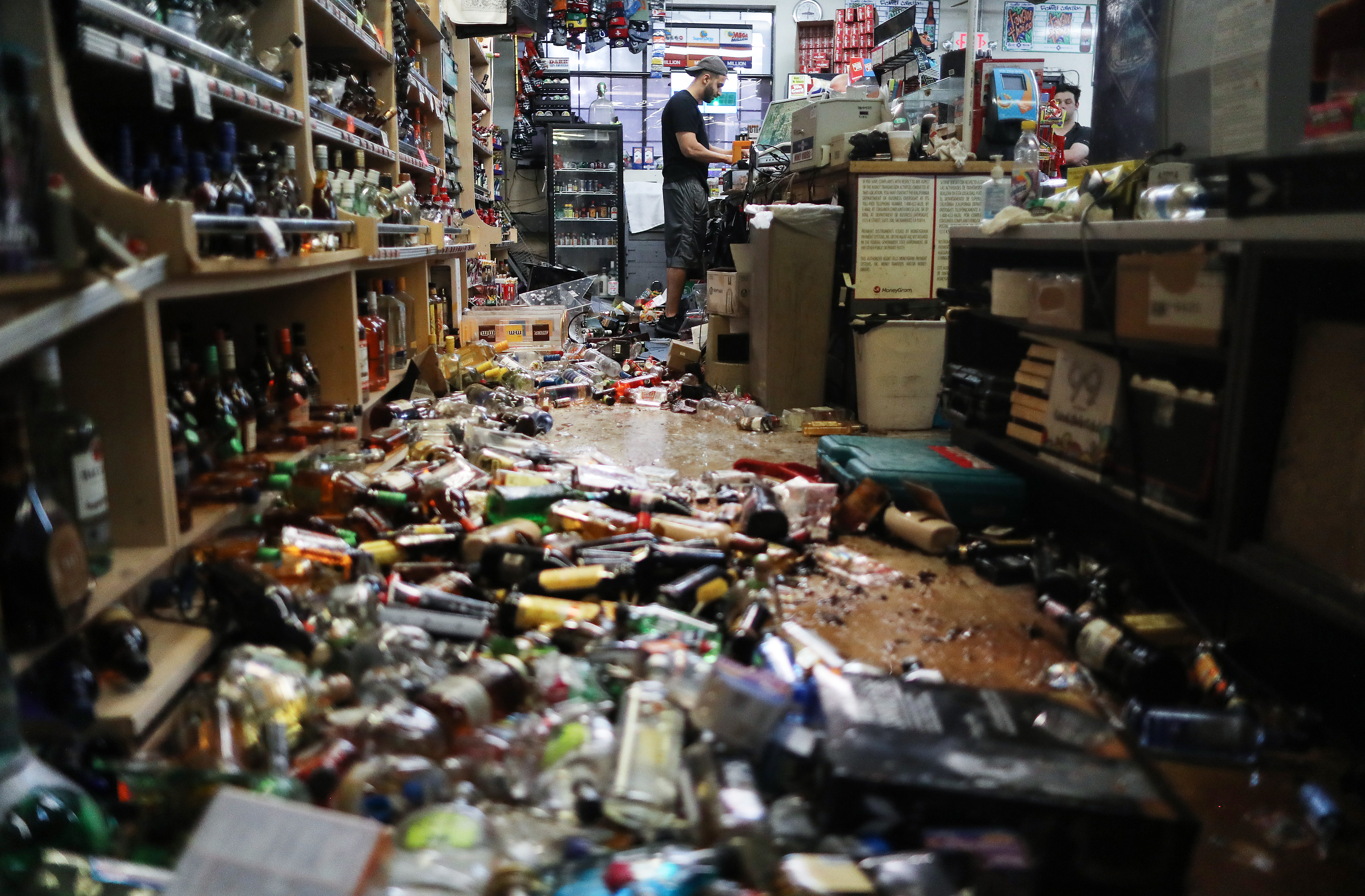 An employee works at the cash register at Ridgecrest Market, near broken bottles scattered on the floor, following a 7.1 magnitude earthquake.