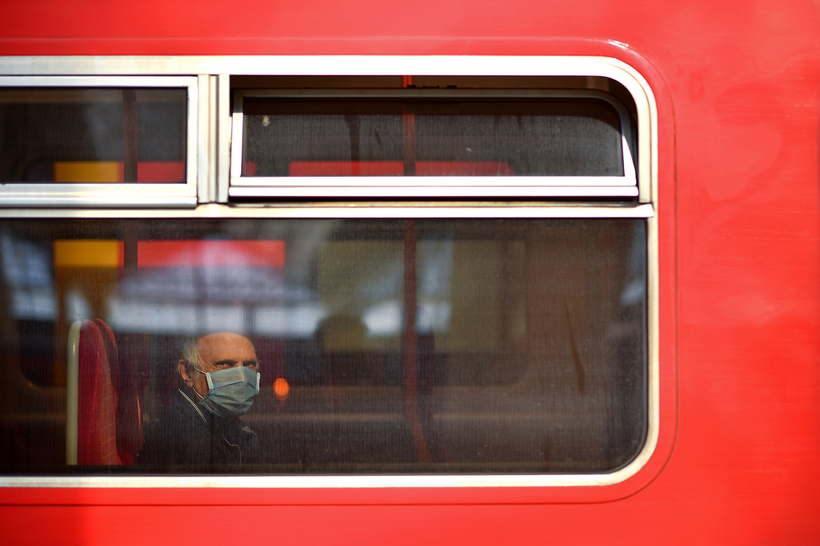 A passenger wearing a face mask sits aboard a train as it arrives at Waterloo Train station in London on Monday.