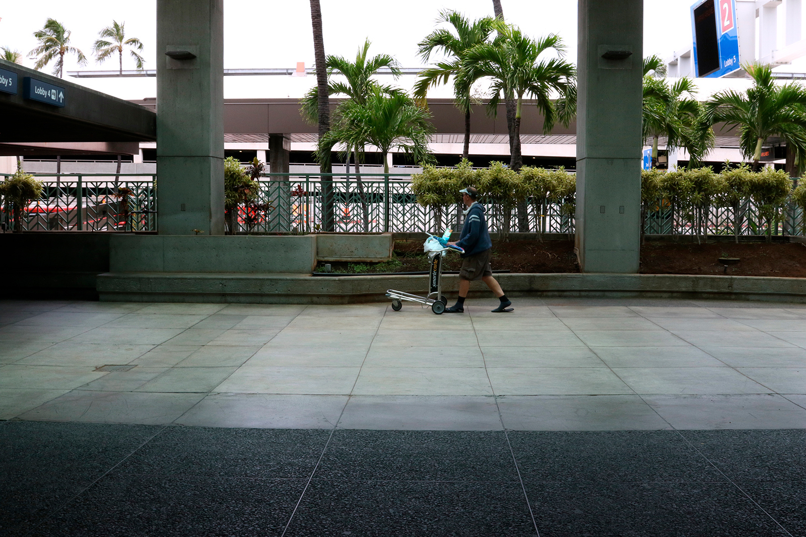 In this April 21 photo, a man pushes a cart at the international airport in Honolulu.