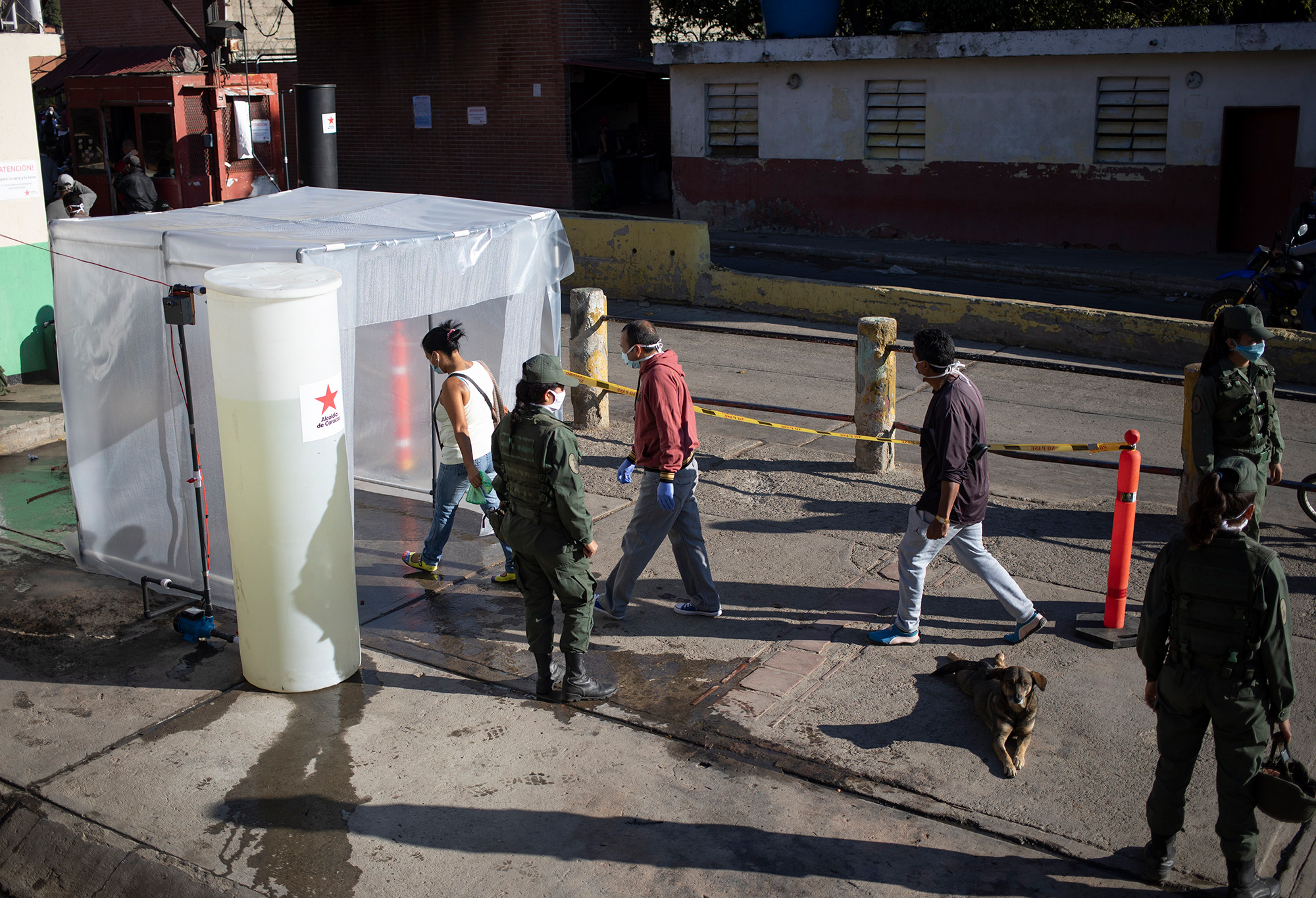 People go through a decontamination chamber as a preventive measure against the spread of the coronavirus, before entering a popular market in Caracas, Venezuela, on Wednesday, March 18.