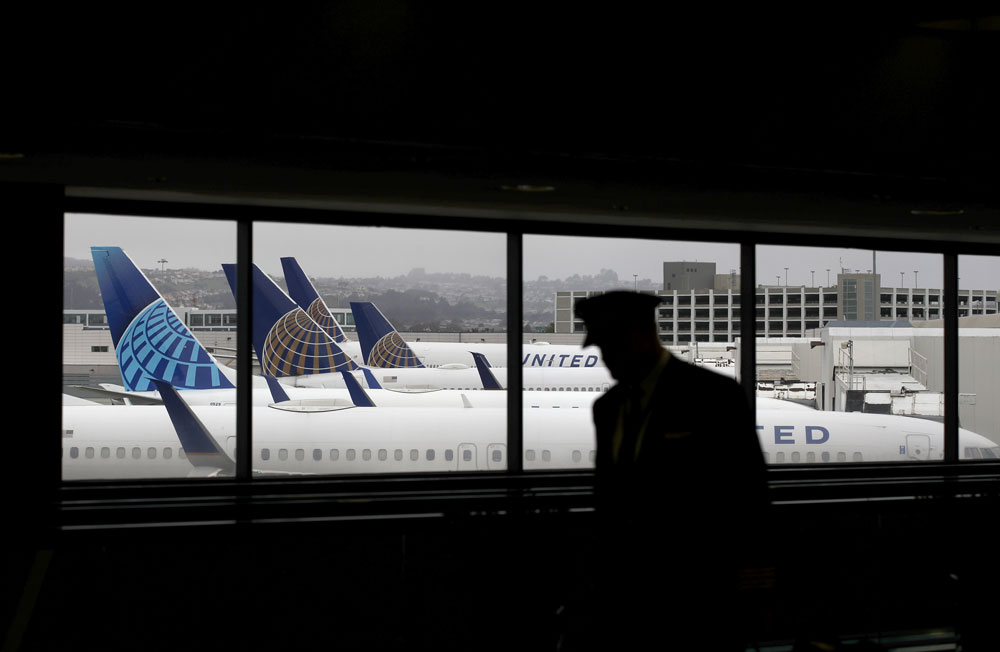 A pilot walks by United Airlines planes as they sit parked at gates at San Francisco International Airport on April 12, in San Francisco, California.
