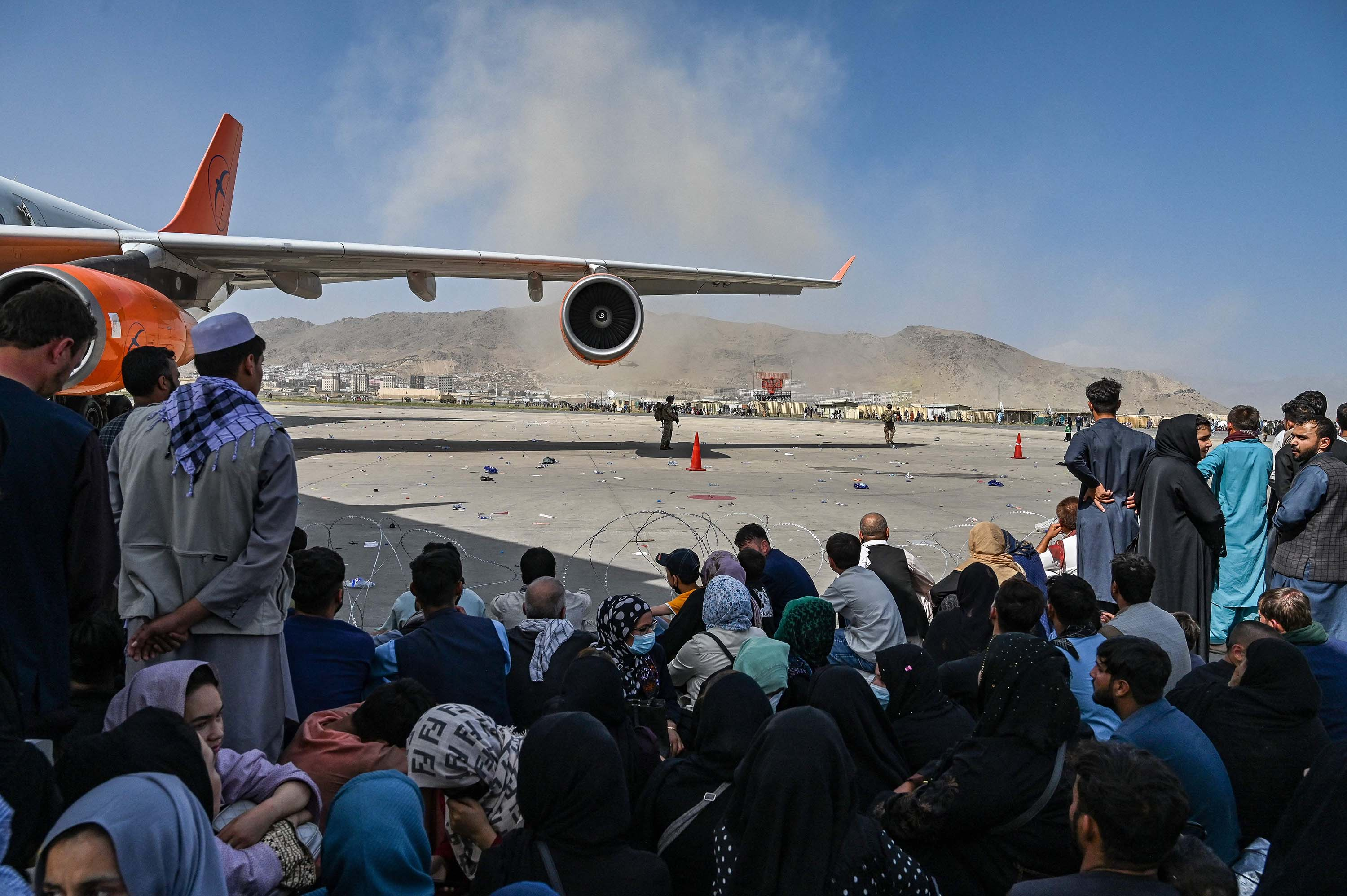 People wait to leave Kabul airport on August 16.