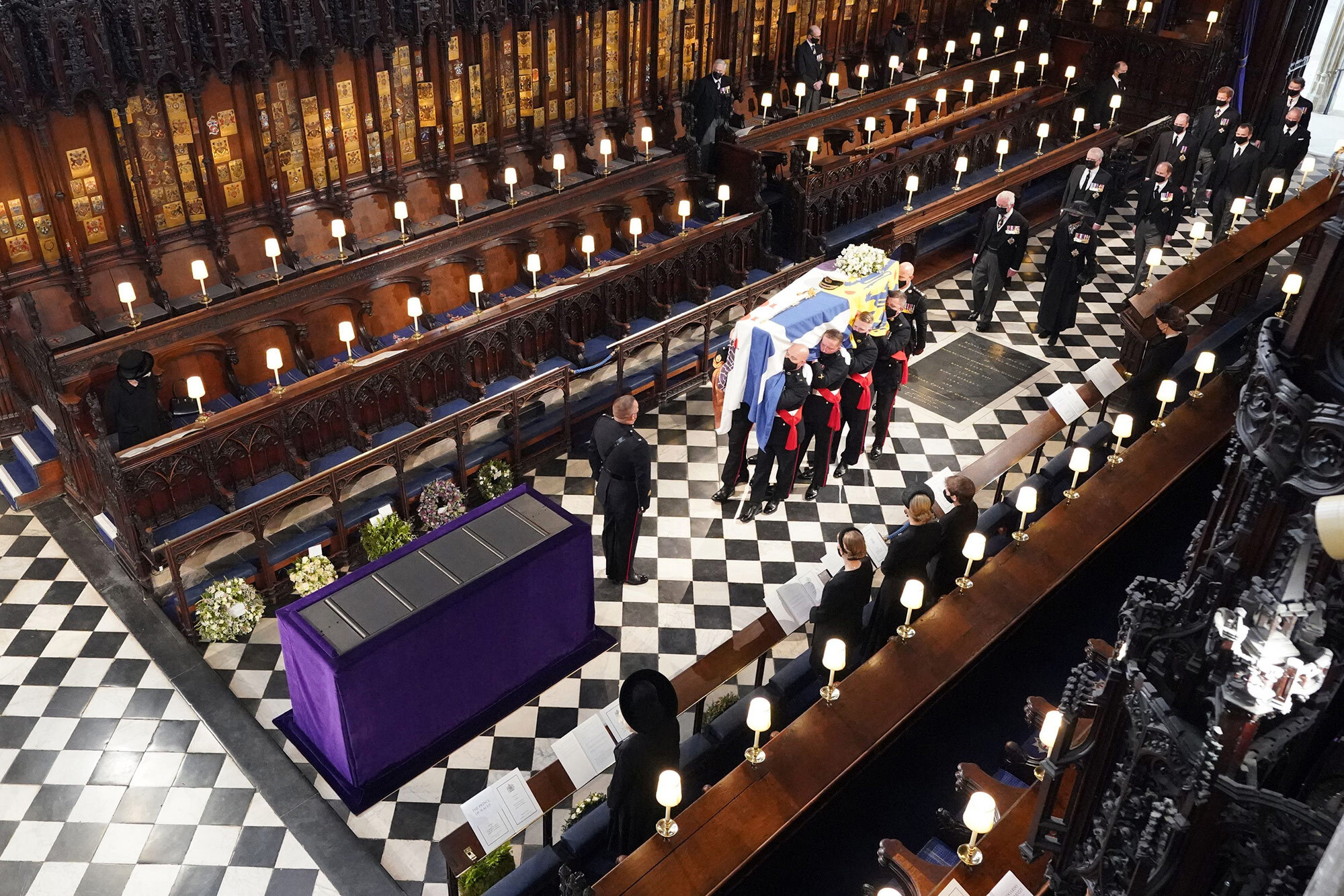 Queen Elizabeth II, left, watches as pallbearers carry Prince Philip's coffin during his funeral inside St. George's Chapel in Windsor Castle, on April 17.