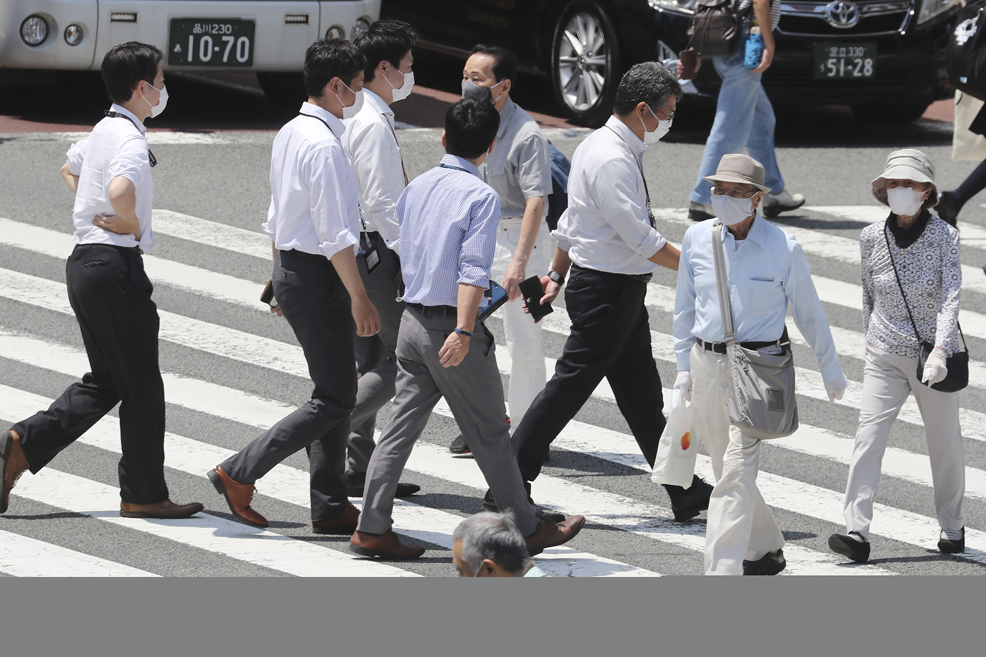 People wearing face masks to help protect against the spread of the coronavirus walk on a street in Tokyo, Japan, on Tuesday, August 4.