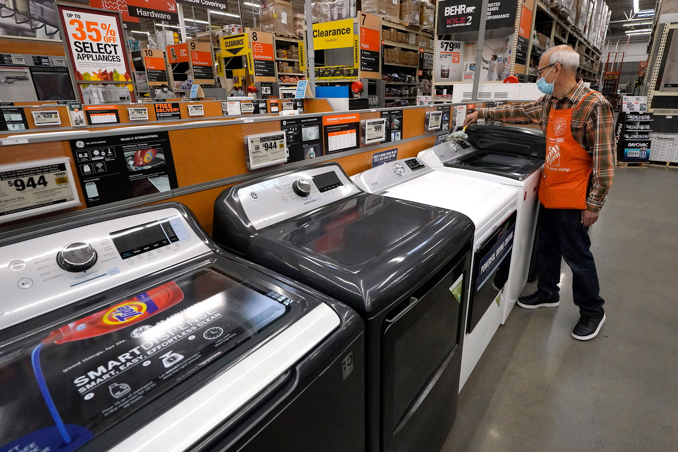 In this photo, taken October 29, 2020, an employee wears a mask indoors while dusting washers on a display, at a Home Depot location, in Boston.
