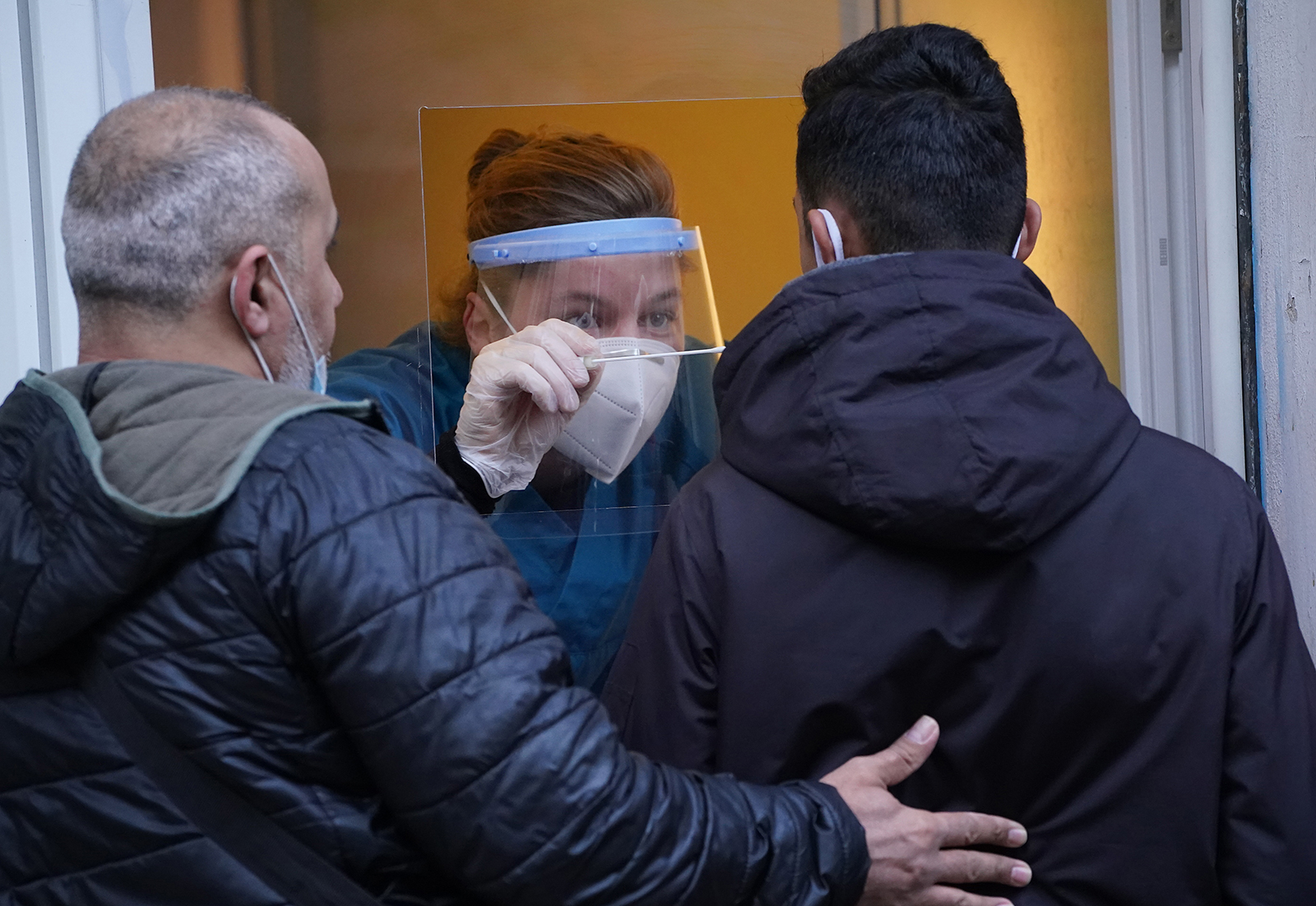 A medical assistant takes a throat swab sample from a man through the window of a medical practice for a coronavirus test in Berlin, Germany, on October 12.