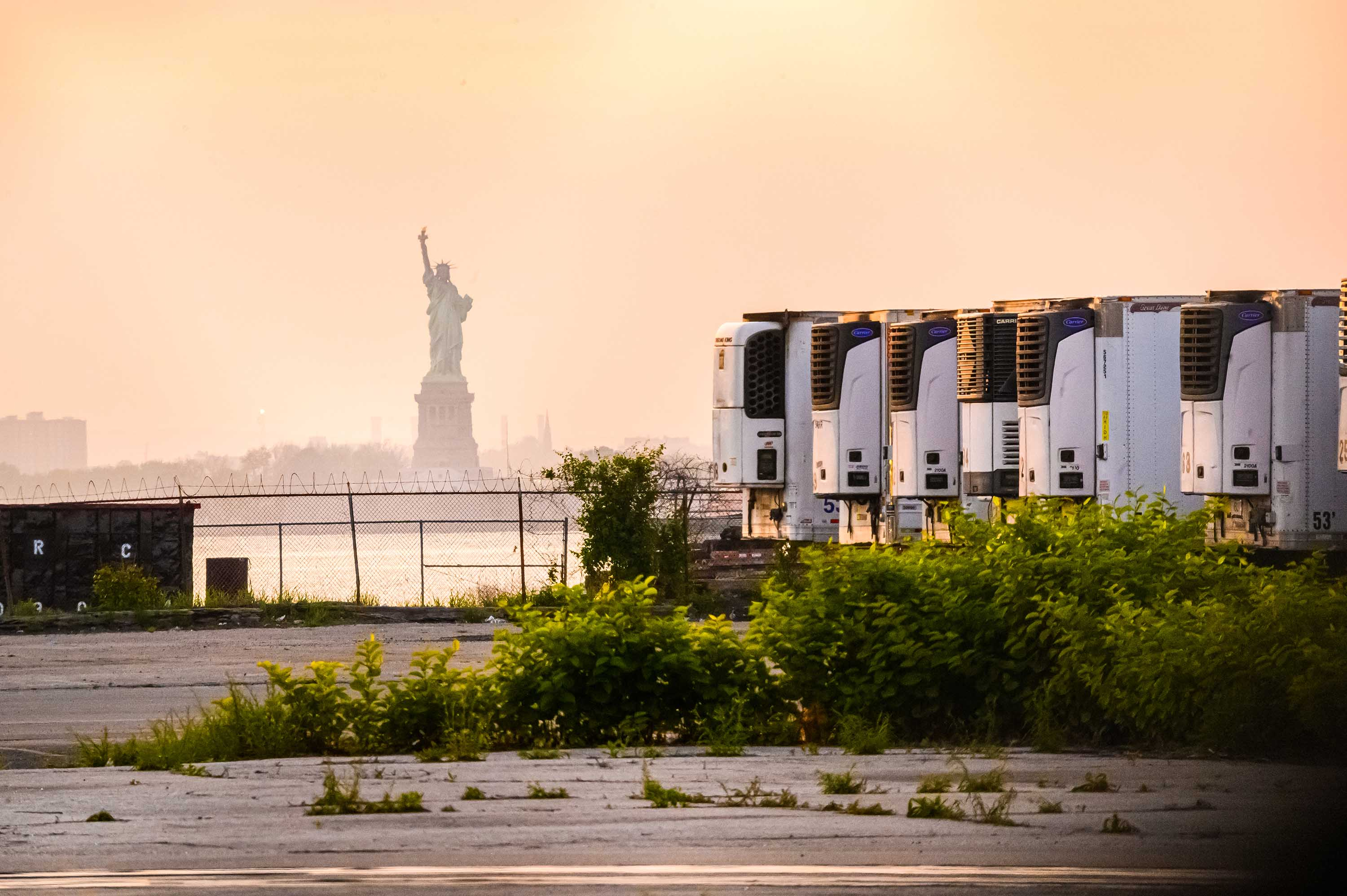 The Statue of Liberty is seen behind refrigeration trucks that function as temporary morgues for coronavirus victims at the South Brooklyn Marine Terminal in New York City on May 25.