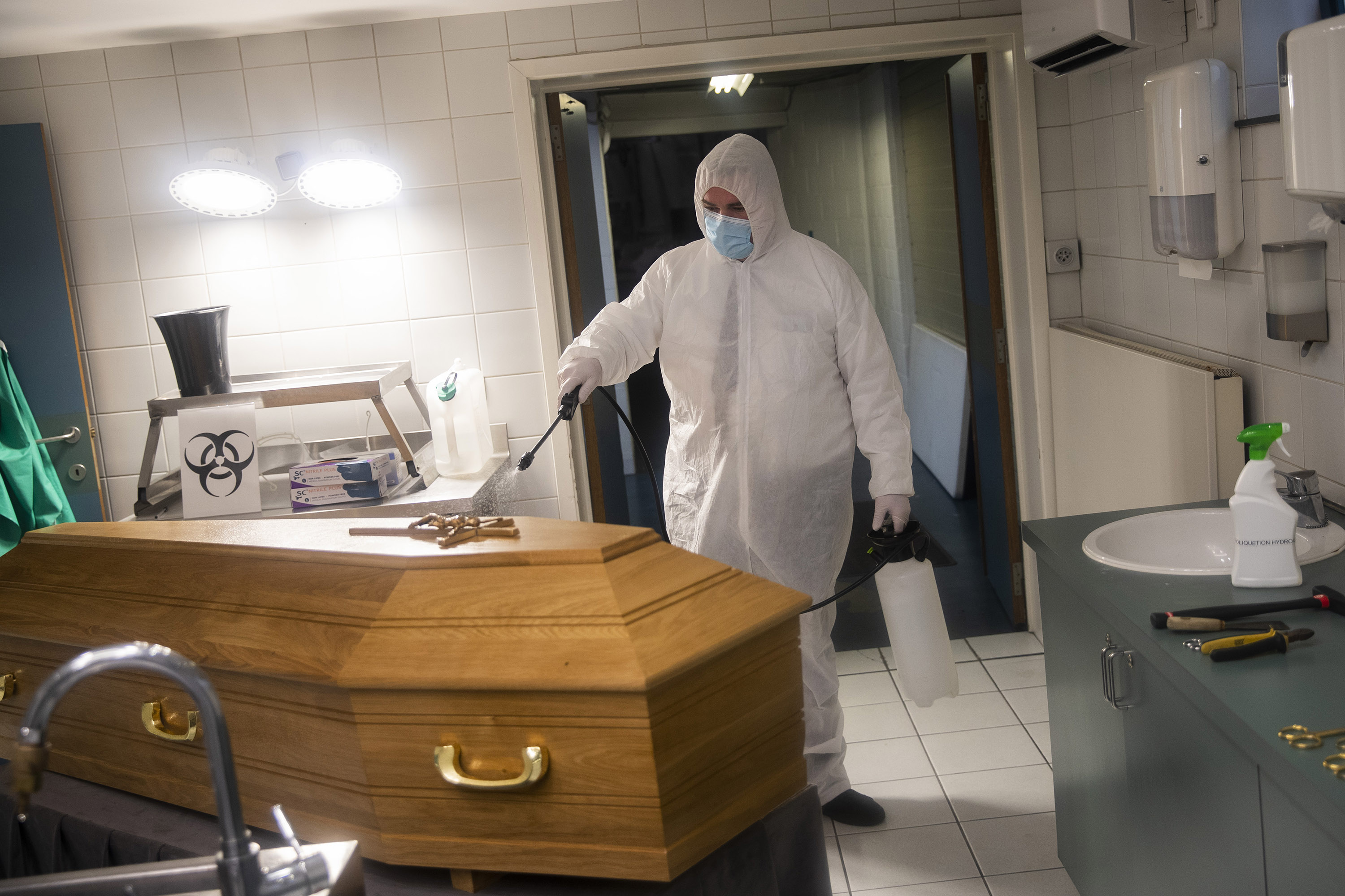 A worker disinfects the casket of someone who died from coronavirus at the Fontaine funeral home in Charleroi, Belgium, on November 17.