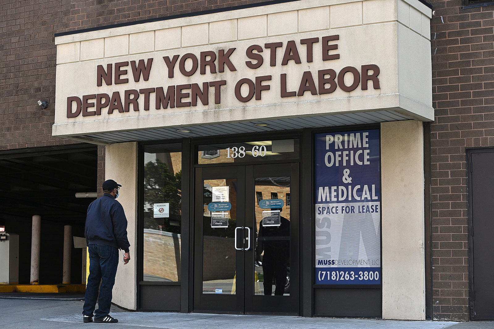 A man reads a sign on the door of the New York State Department of Labor offices in the New York City borough of Queens, on Thursday, April 2.