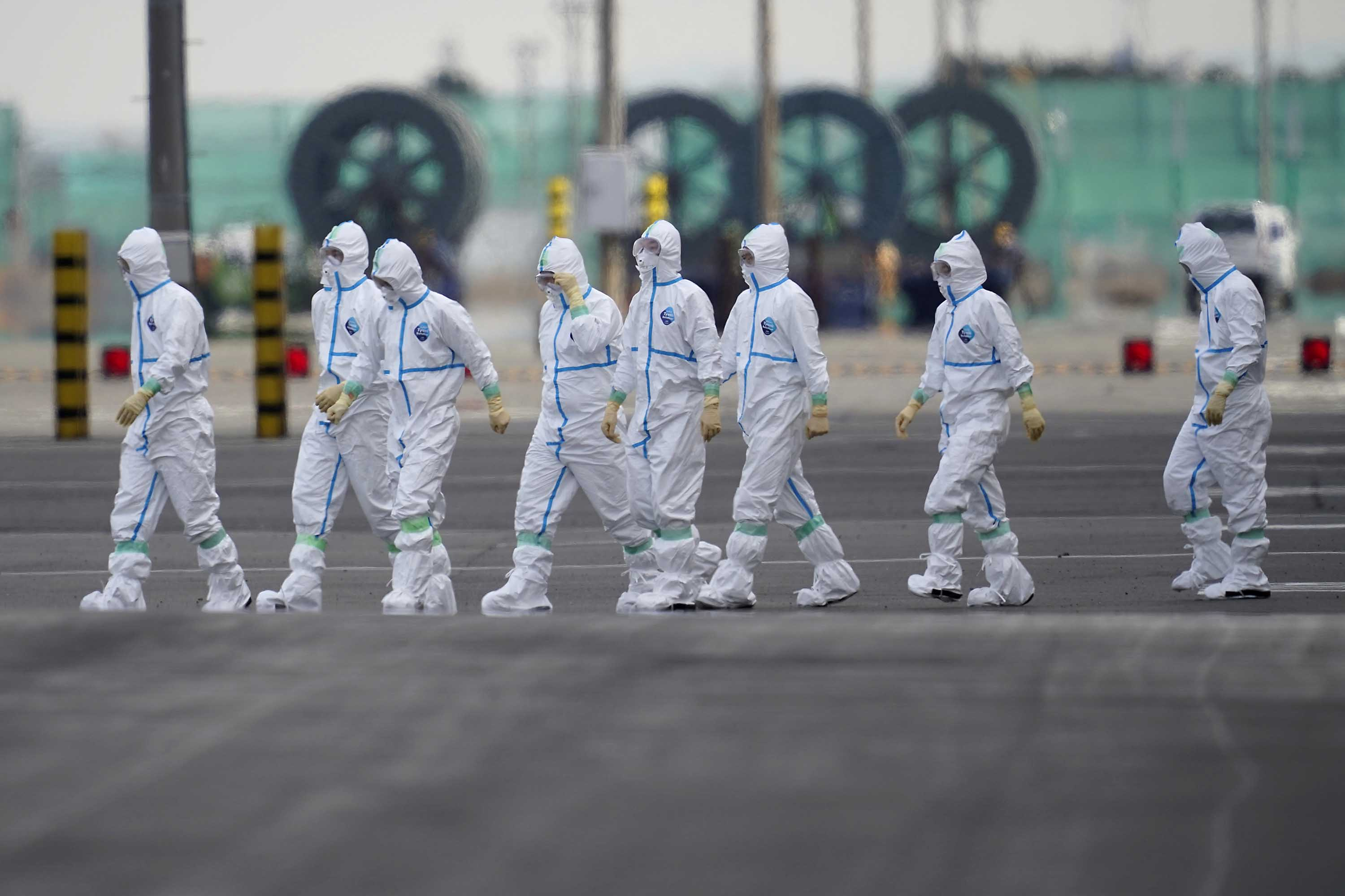 Workers in protective gear are seen near the Diamond Princess cruise ship docked in Yokohama, Japan on Friday.