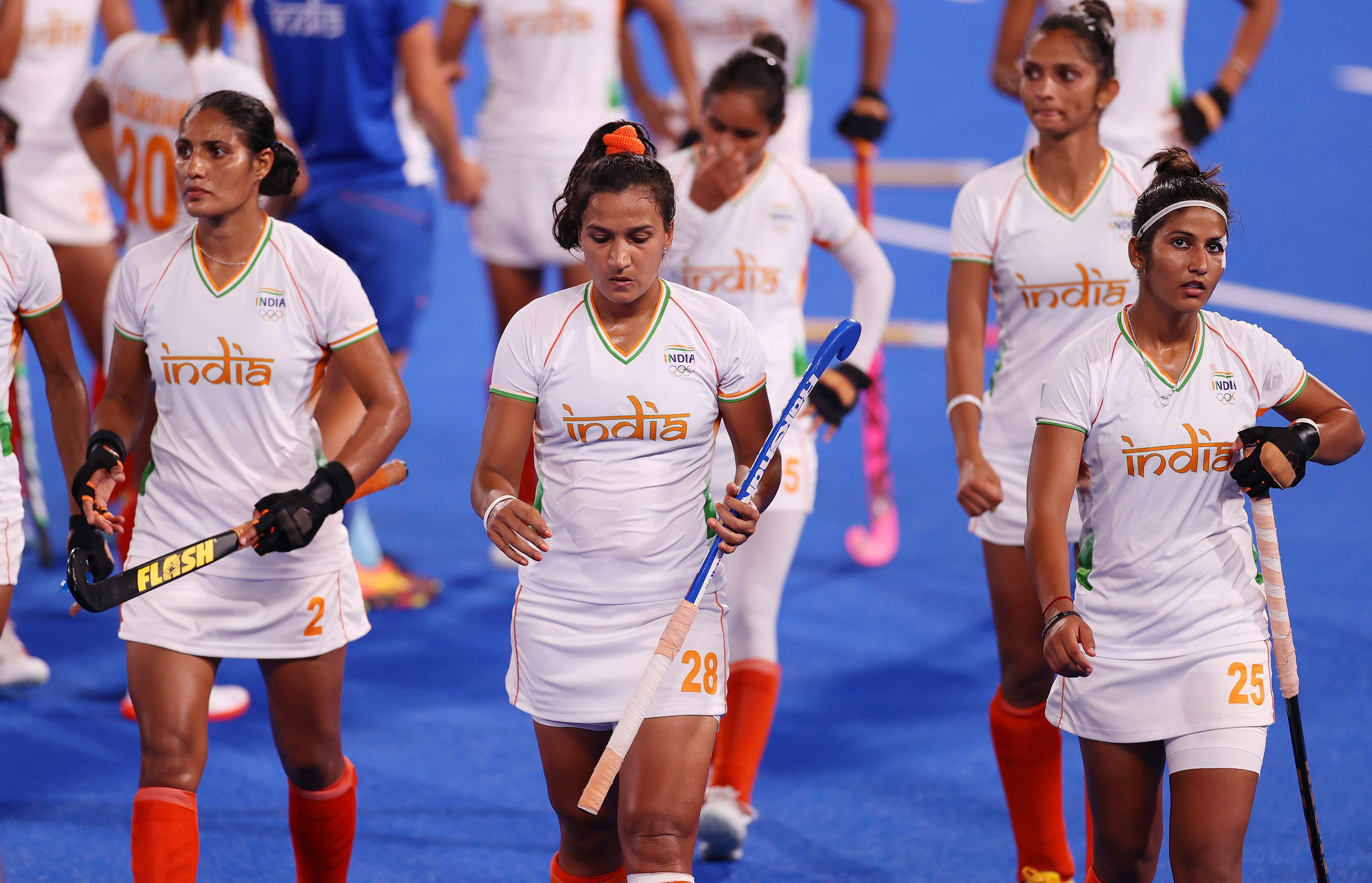 Members of India's hockey team leave the pitch following a loss in the semifinal match against Argentina  on August 4.