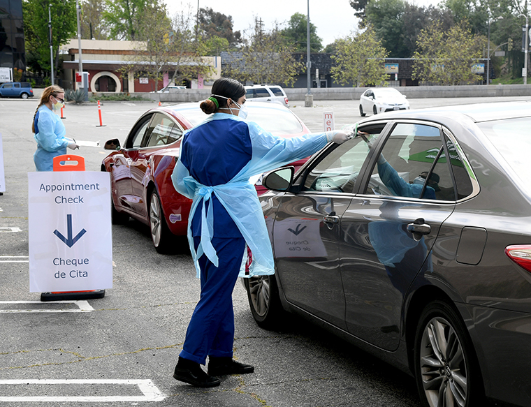 Workers wearing personal protective equipment gather the tests administered from people's cars as Mend Urgent Care hosts a drive-thru testin at the Westfield Fashion Square on Monday,April 13, in Los Angeles
