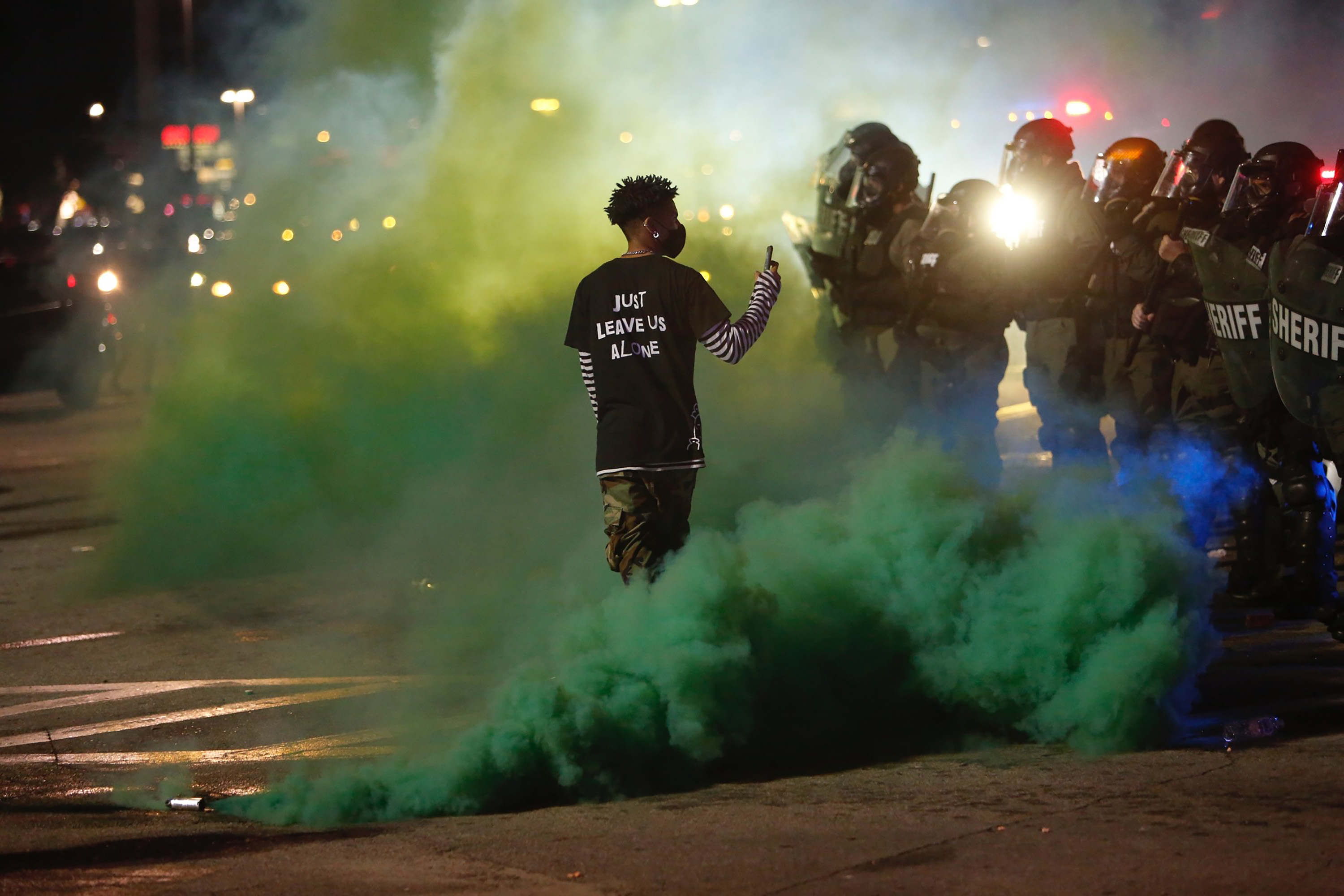 A protester walks through smoke while filming Hillsborough County sheriff's deputies in Tampa, Florida, on May 30.