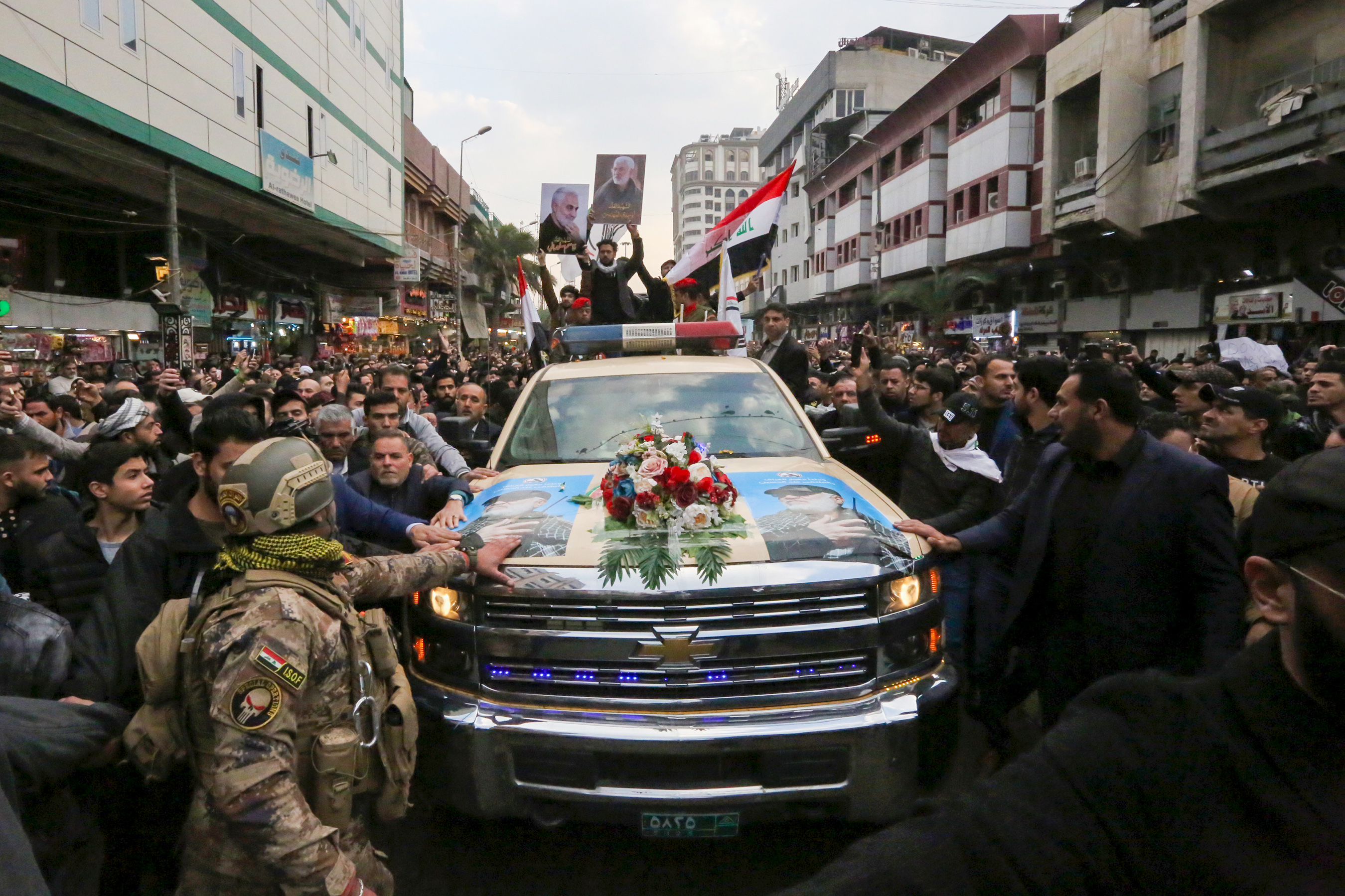 Mourners surround a car carrying the coffin of Iranian commander Qasem Soleimani in Baghdad, on January 4, 2020.