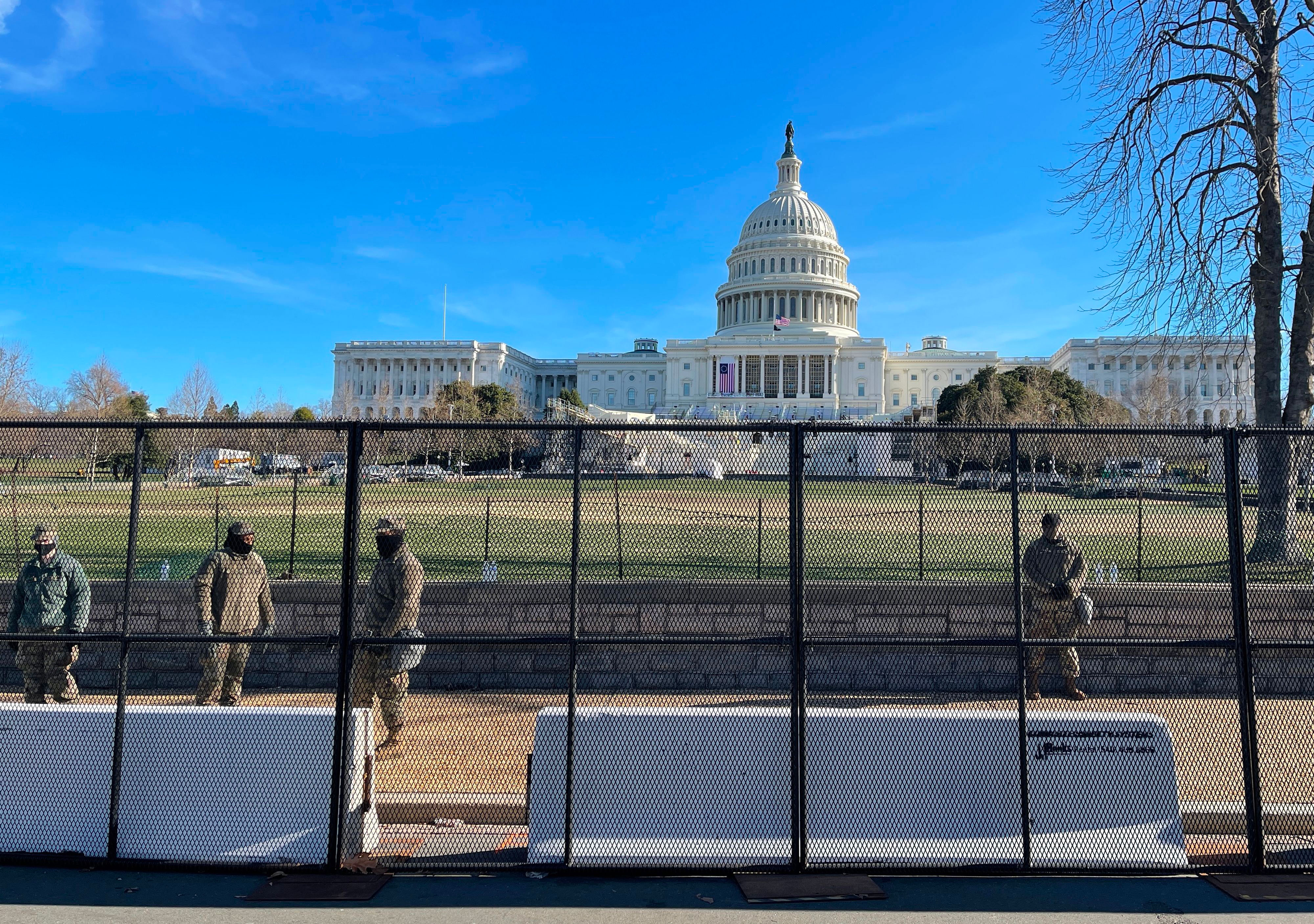 National Guard soldiers stand behind a security fence near the Capitol on January 9.