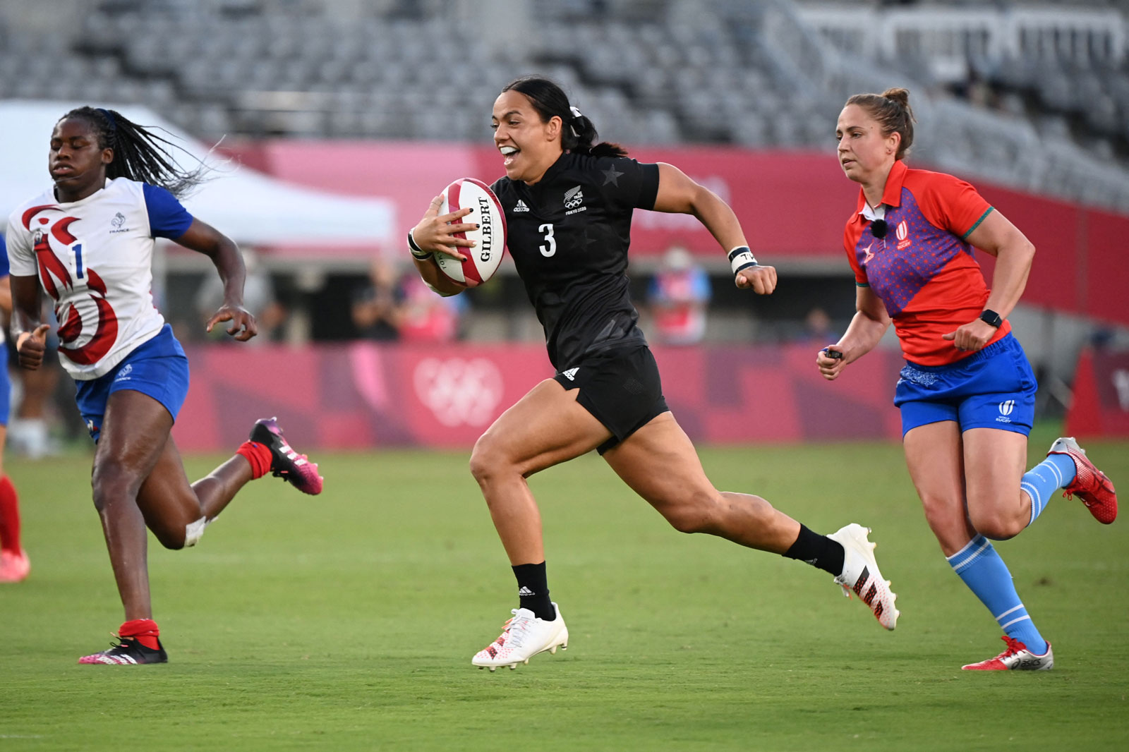 New Zealand's Stacey Fluhler (C) runs to score a try in the women's rugby sevens final between New Zealand and France at the Tokyo Stadium.