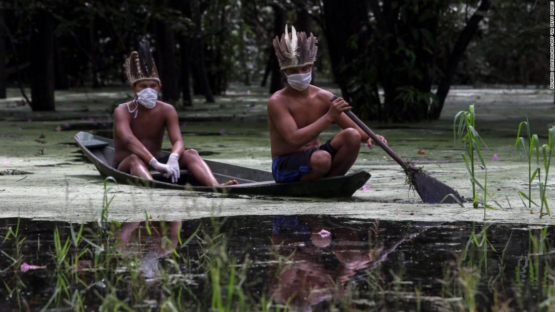 Satere-mawe indigenous men navigate the Ariau river during the COVID-19 novel coronavirus pandemic at the Sahu-Ape community, 80 km of Manaus, Amazonas State, Brazil, on May 5, 2020.