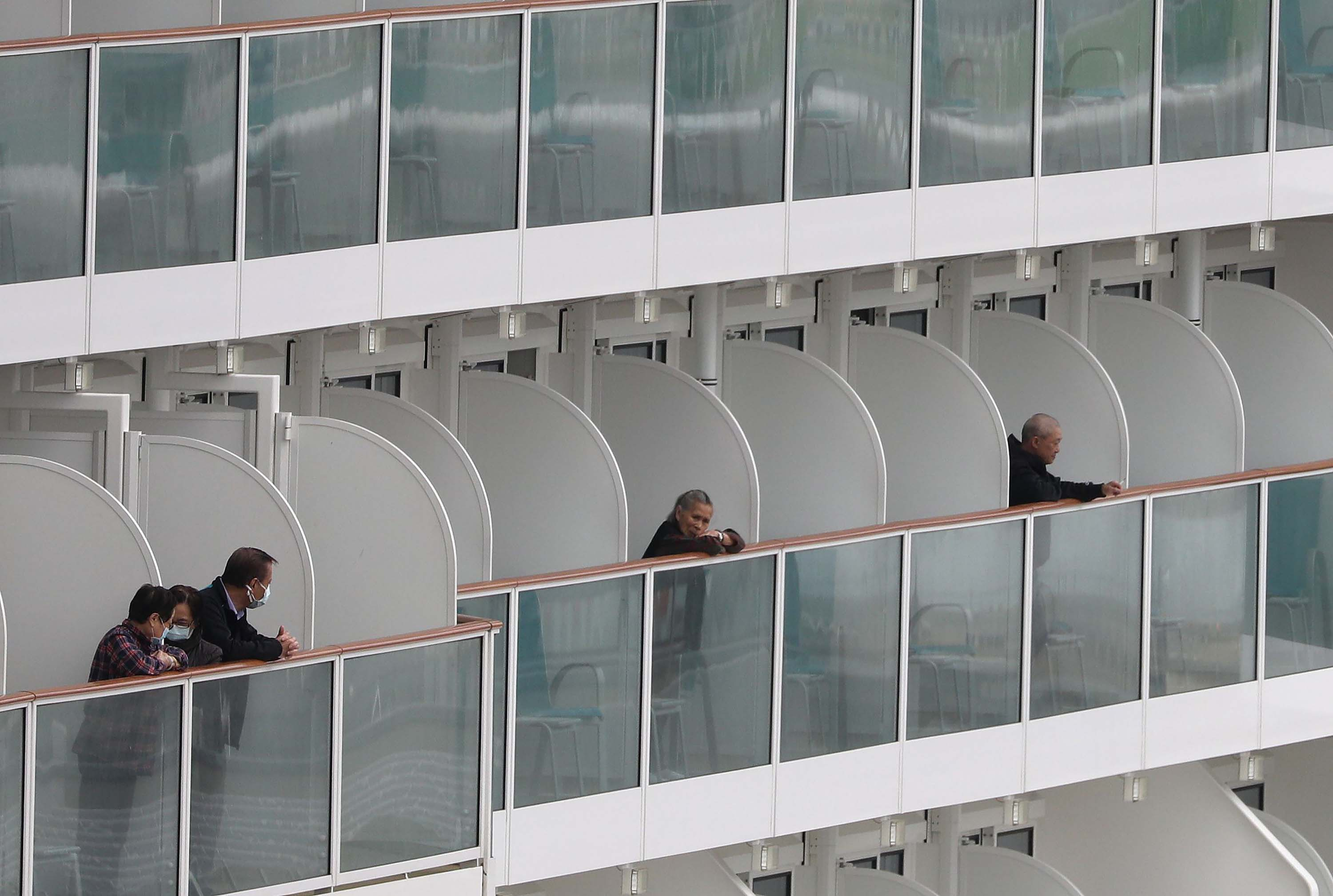 Passengers look out from balconies aboard the World Dream cruise liner docked at the Kai Tak Cruise Terminal in Hong Kong on Wednesday.