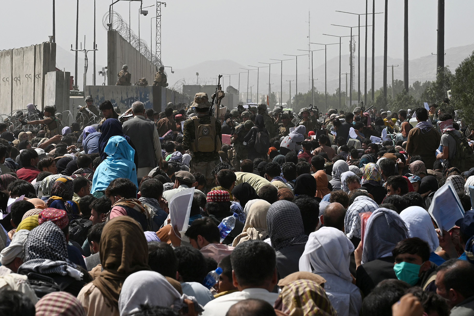 Afghans gather on a roadside near the military part of the airport in Kabul on August 20.