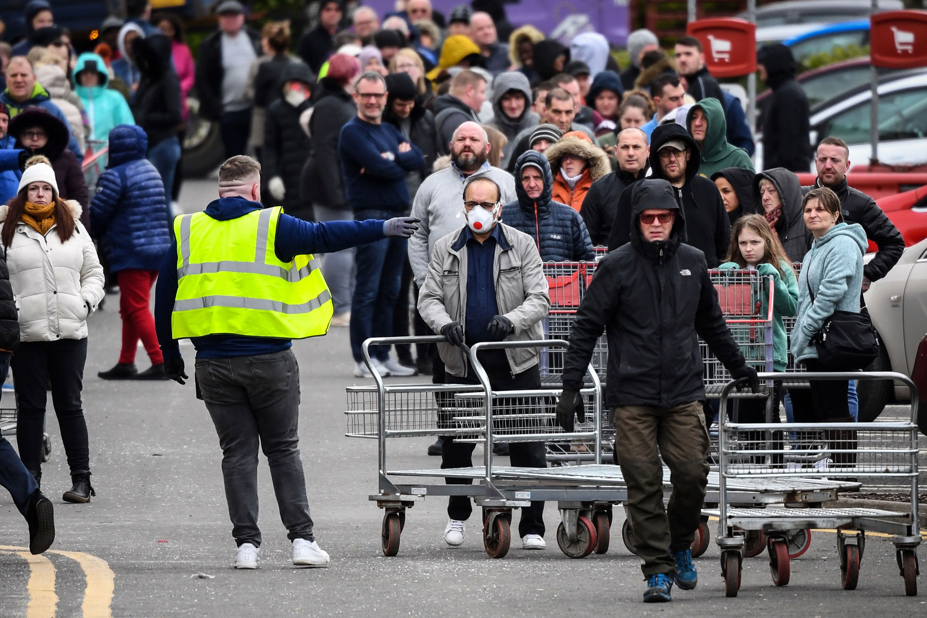 People wait in line at a Costco in Glasgow, Scotland, before it opens on March 21.