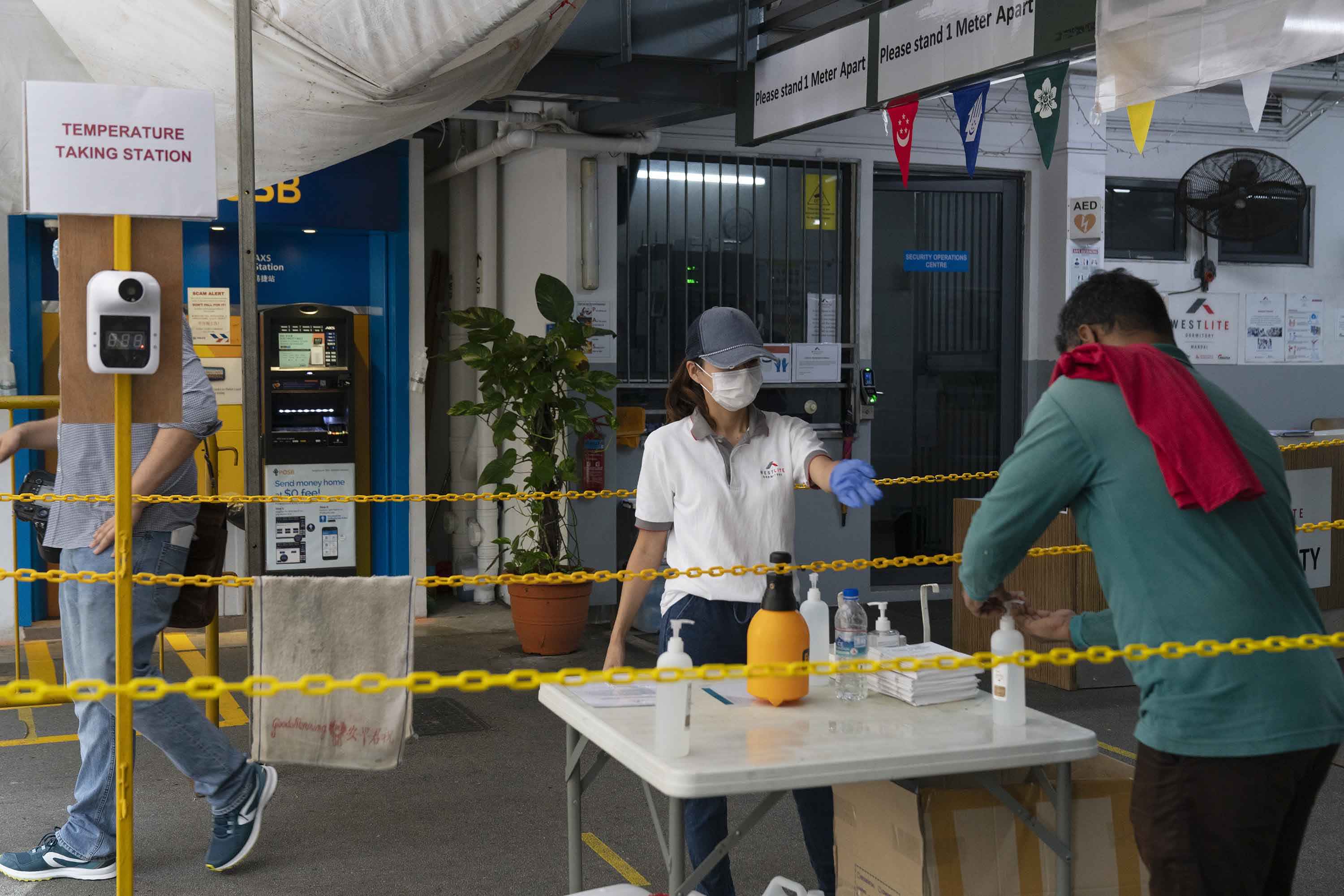 A worker uses hand sanitizer at the entrance to the Westlite Mandai worker dormitory in Singapore, in August.