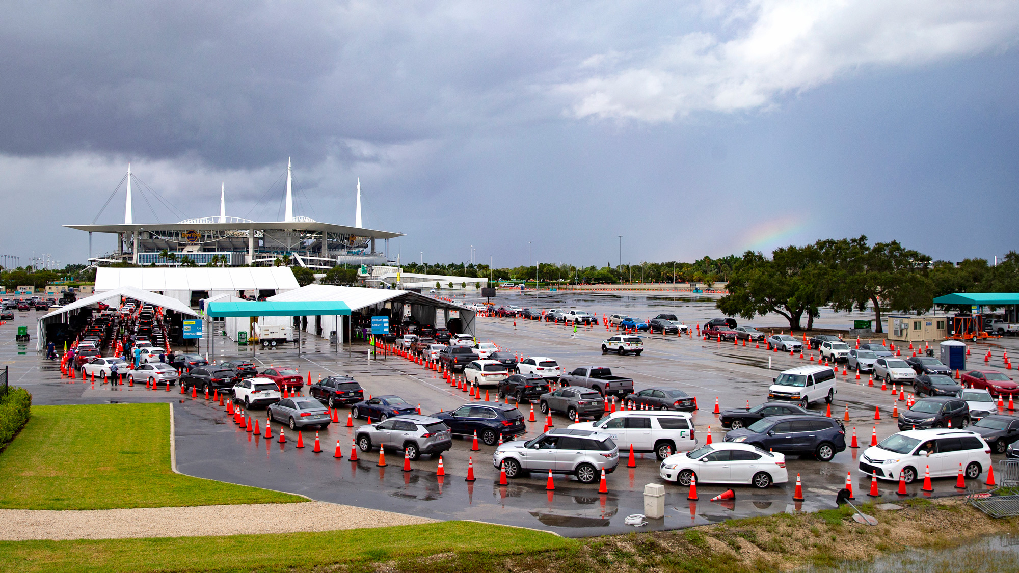 Vehicles line up as healthcare workers help to check-in people for testing at the COVID-19 drive-thru testing center at Hard Rock Stadium in Miami Gardens, Florida, on November 22.