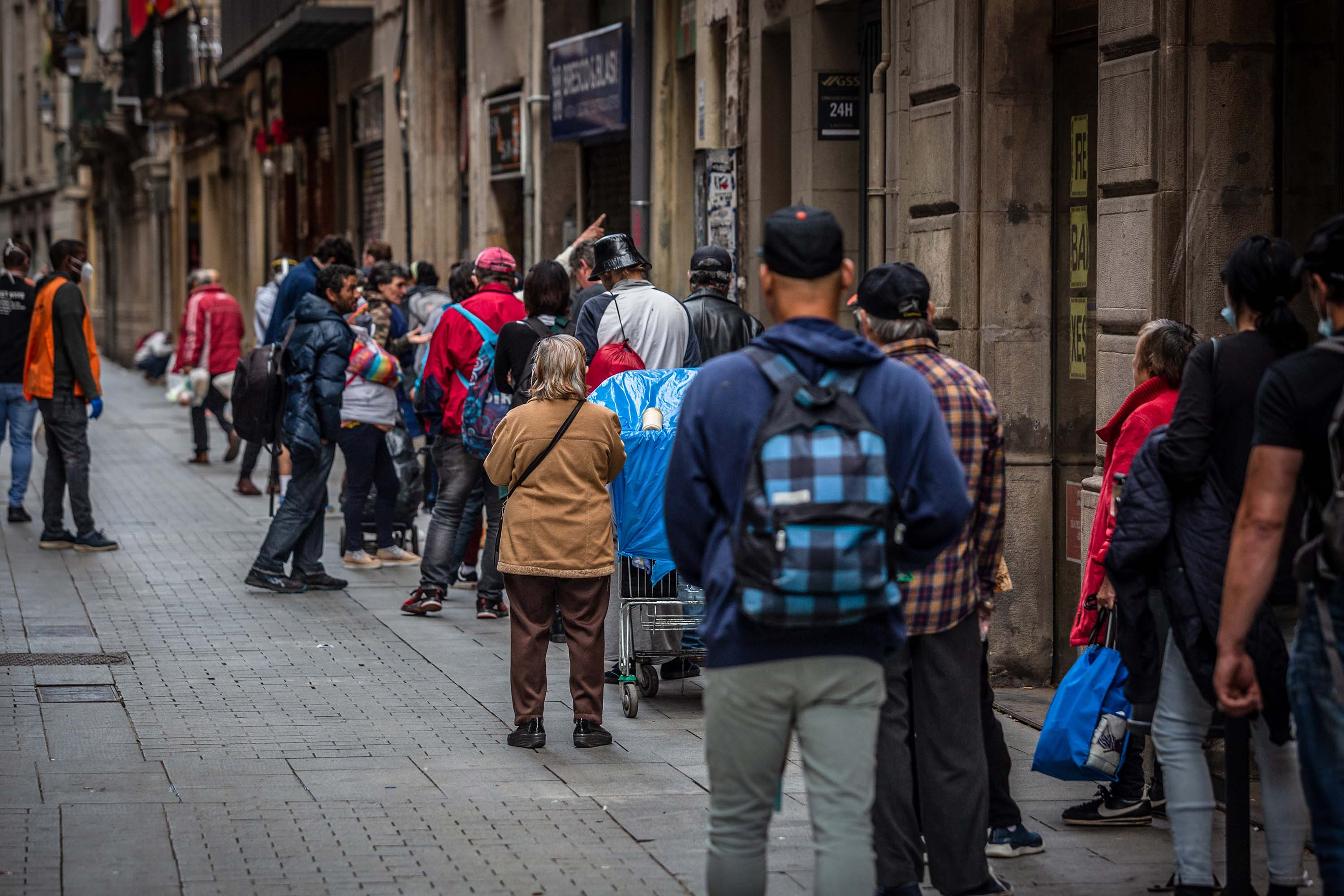 People queue along a street to collect food aid from a distribution point at a church in Barcelona, Spain, on May 17.