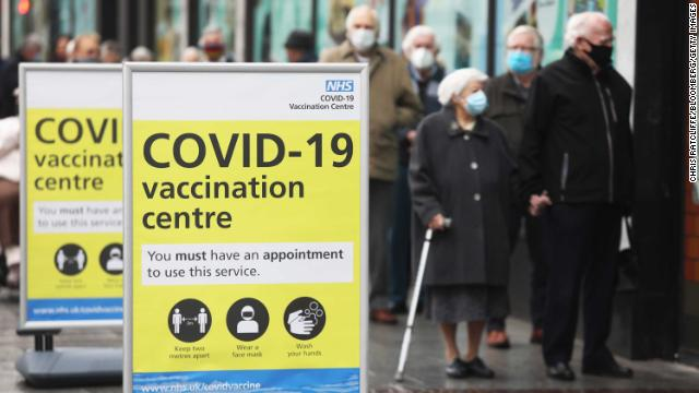 Visitors queue before receiving the AstraZeneca vaccine at a closed down Debenhams department store, in Folkestone on Wednesday