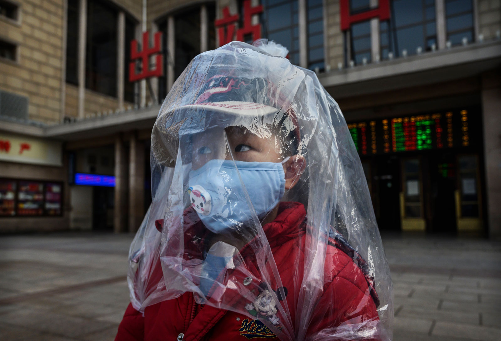 A boy is covered in a plastic bag amid the coronavirus outbreak as he arrives from a train at Beijing Station on February 12, 2020.