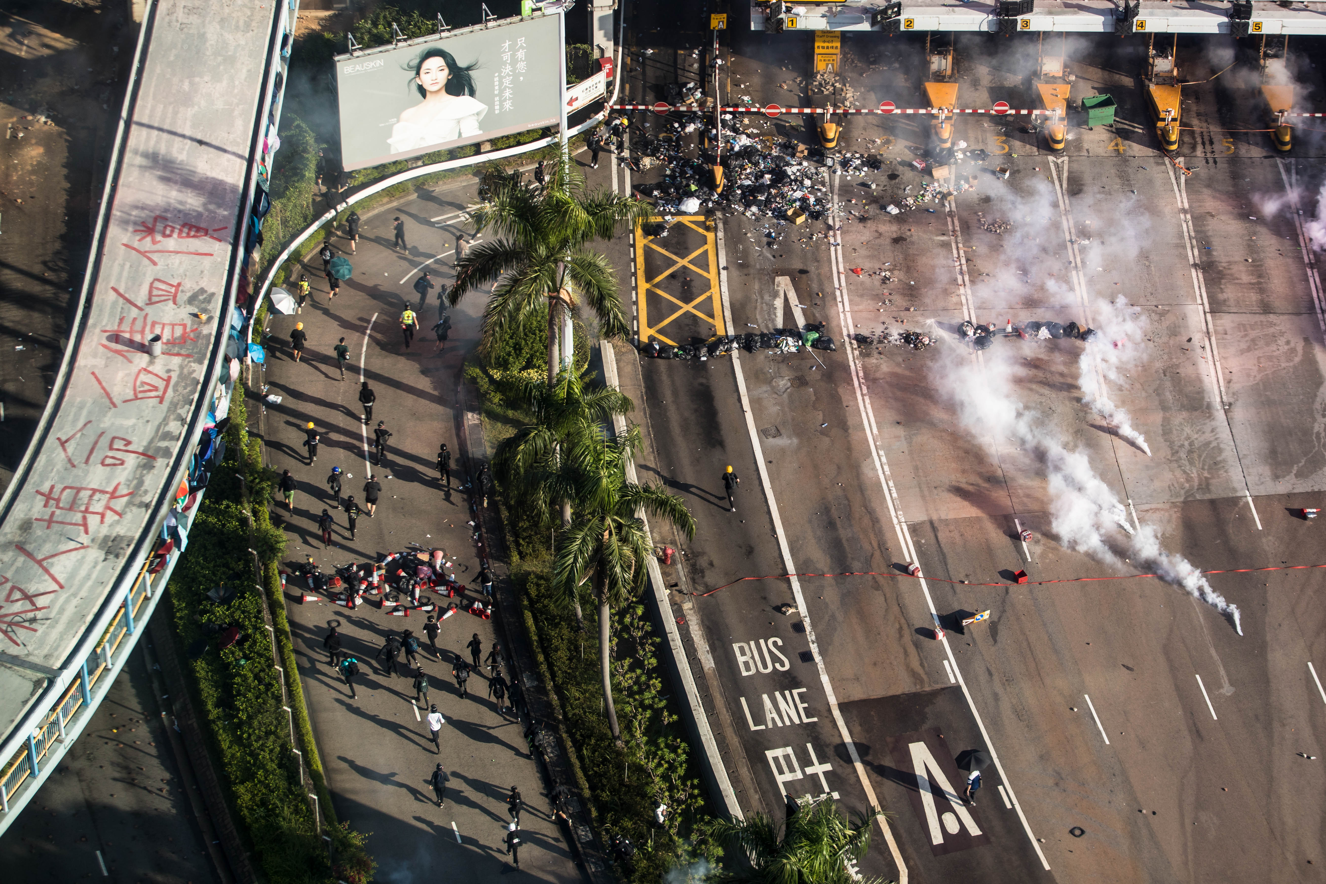 Police fire tear gas as protesters run on a road while trying to leave Hong Kong Polytechnic University in Hung Hom district of Hong Kong on November 18.