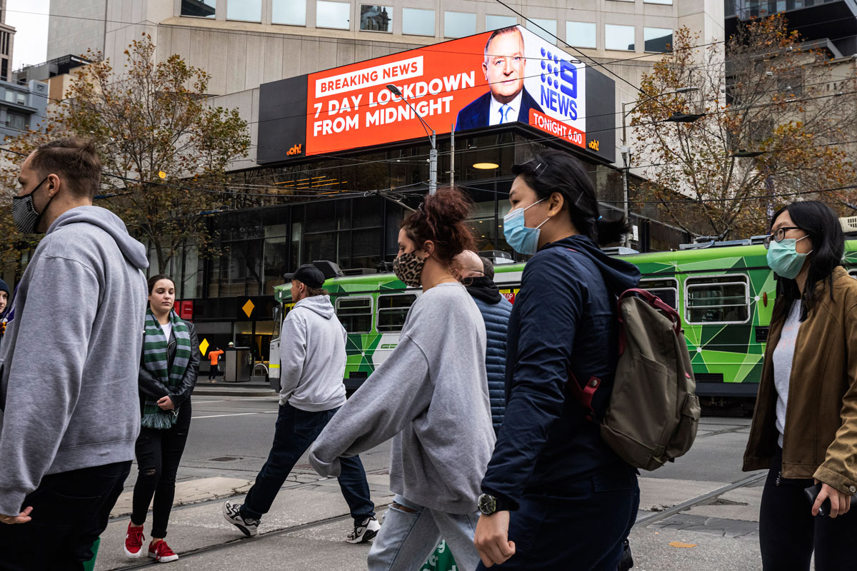 People wearing face masks are seen crossing Bourke Street Mall in front of an LED sign in the background displaying news of the impending seven-day lockdown on May 27 in Melbourne, Australia.