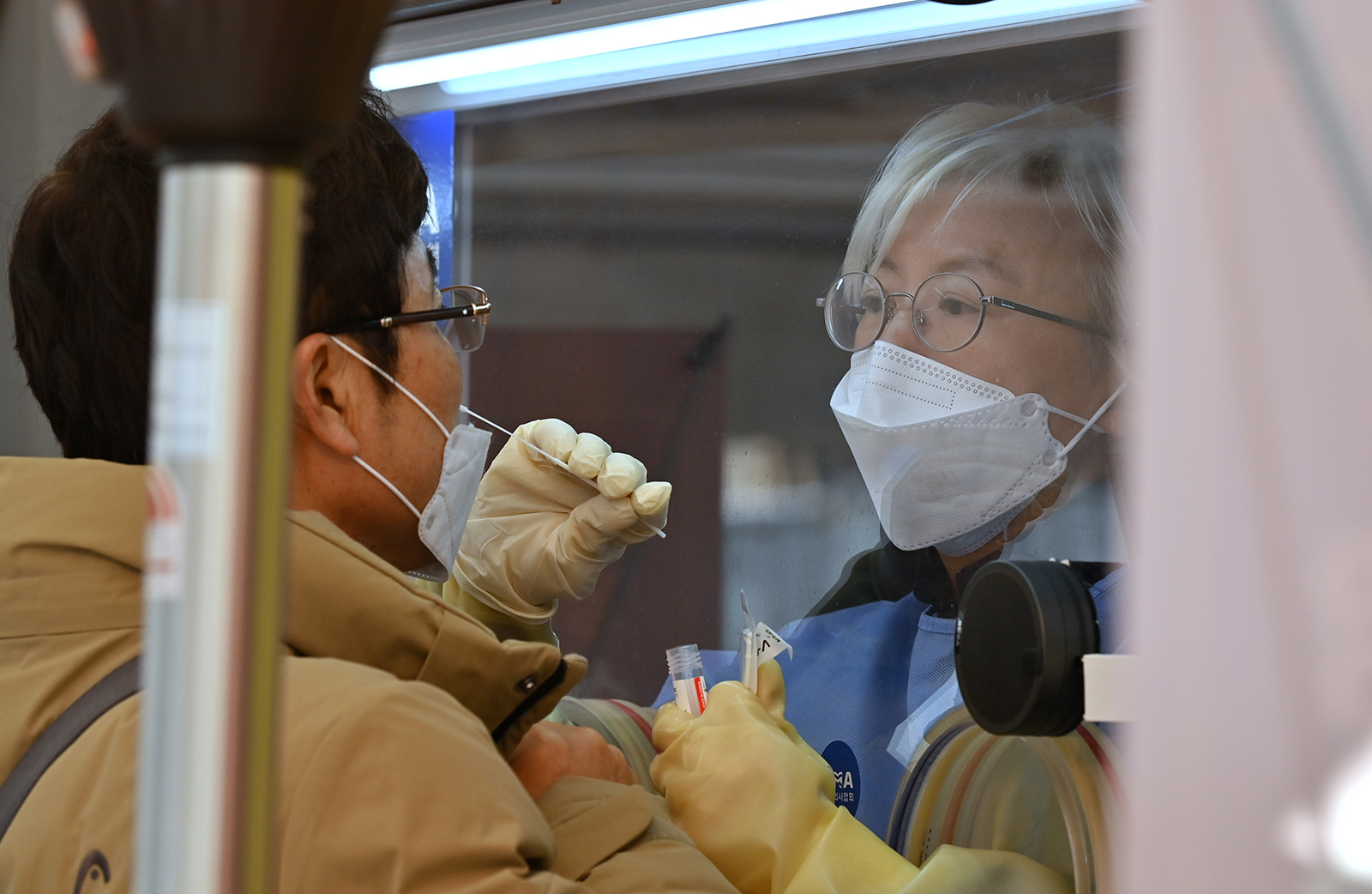 A medical staff member takes a swab from a visitor to test for Covid-19 in Seoul, South Korea, on December 28, 2020.
