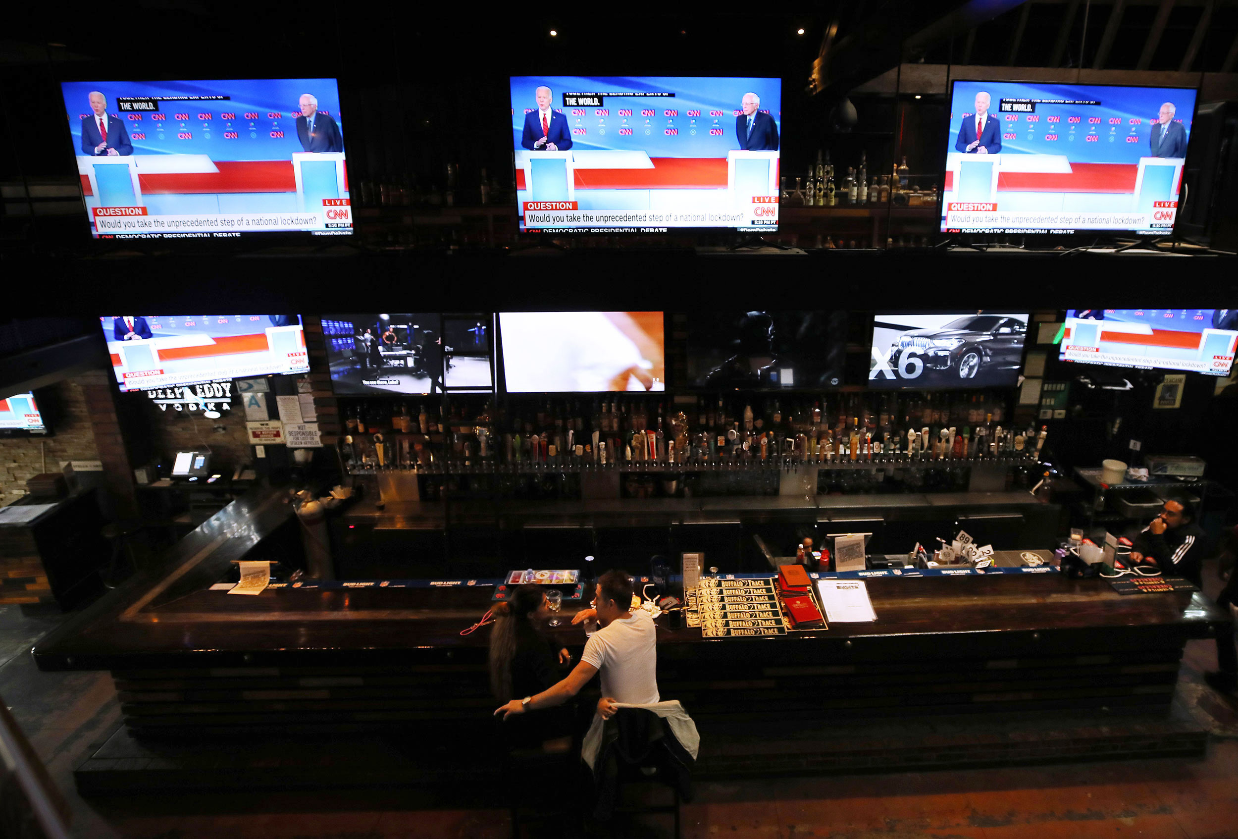 People eat at a nearly empty bar and restaurant in Los Angeles on Sunday night.