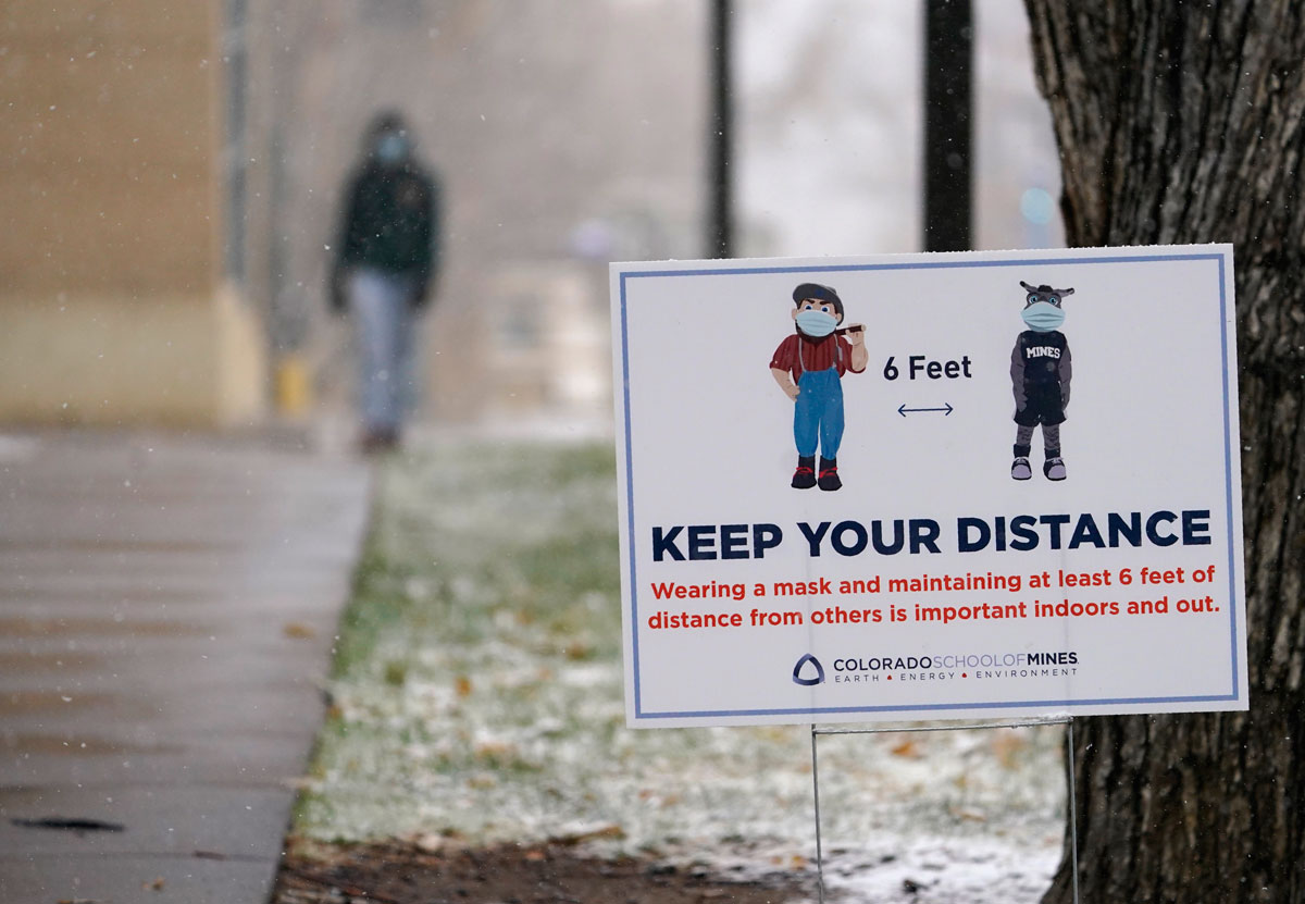 A sign reminds students, faculty and visitors to maintain social distance to combat the spread of the coronavirus while on the campus of the Colorado School of Mines, in Golden, Colorado, on November 9.