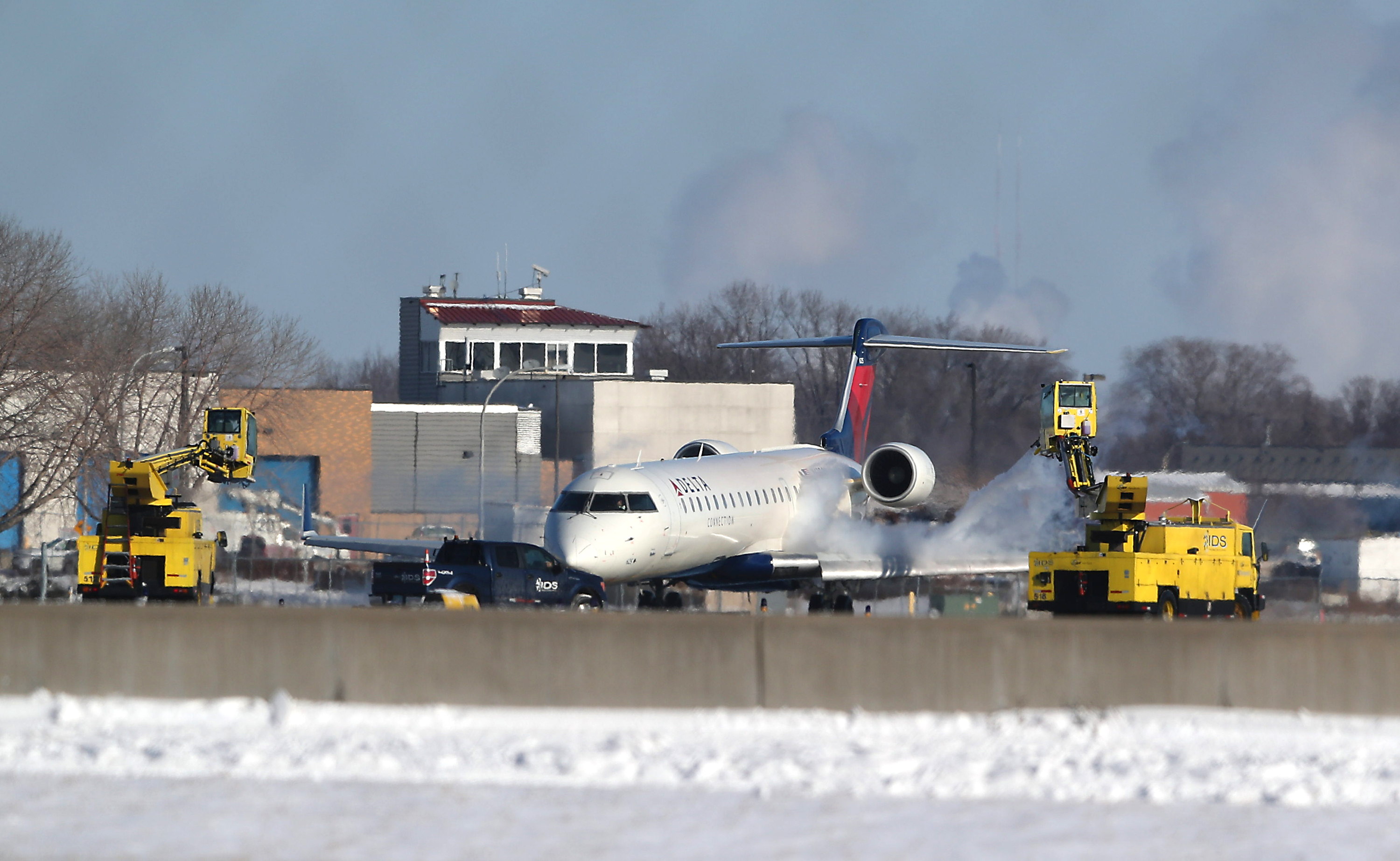 Minneapolis/St. Paul International Airport grounds crews deice an airplane prior to takeoff on Wednesday in Bloomington, Minnesota.