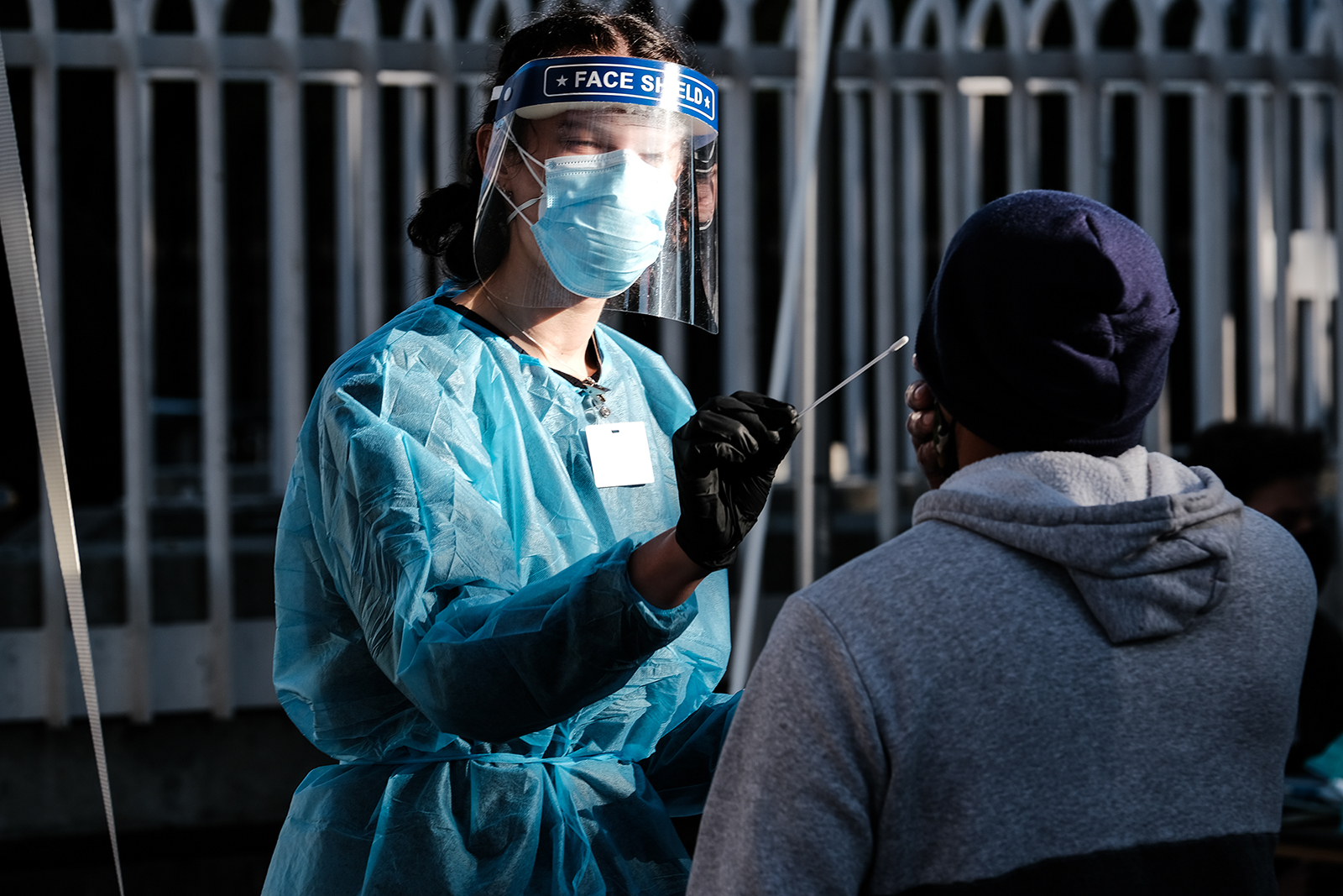 A health care worker administers a test at a Covid-19 testing tent outside a Bay Area Rapid Transit (BART) station in the Mission District of San Francisco, California, on Monday, Nov. 30.