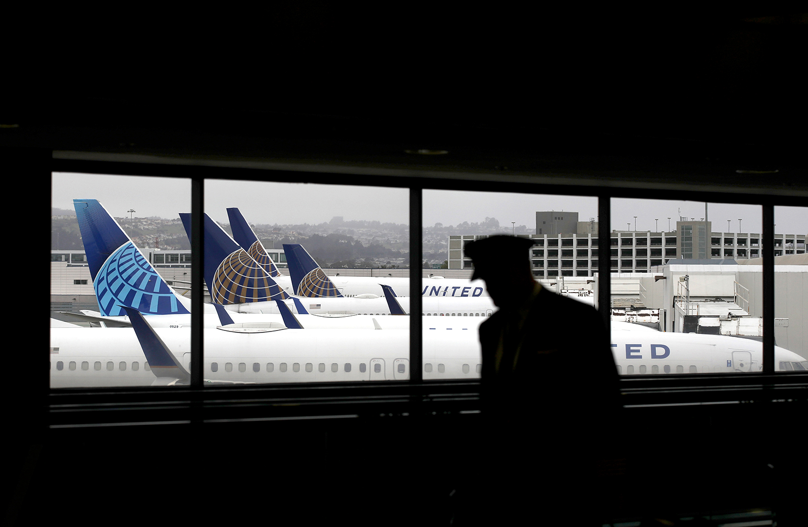 A pilot walks by United Airlines planes as they sit parked at gates at San Francisco International Airport, on April 12.