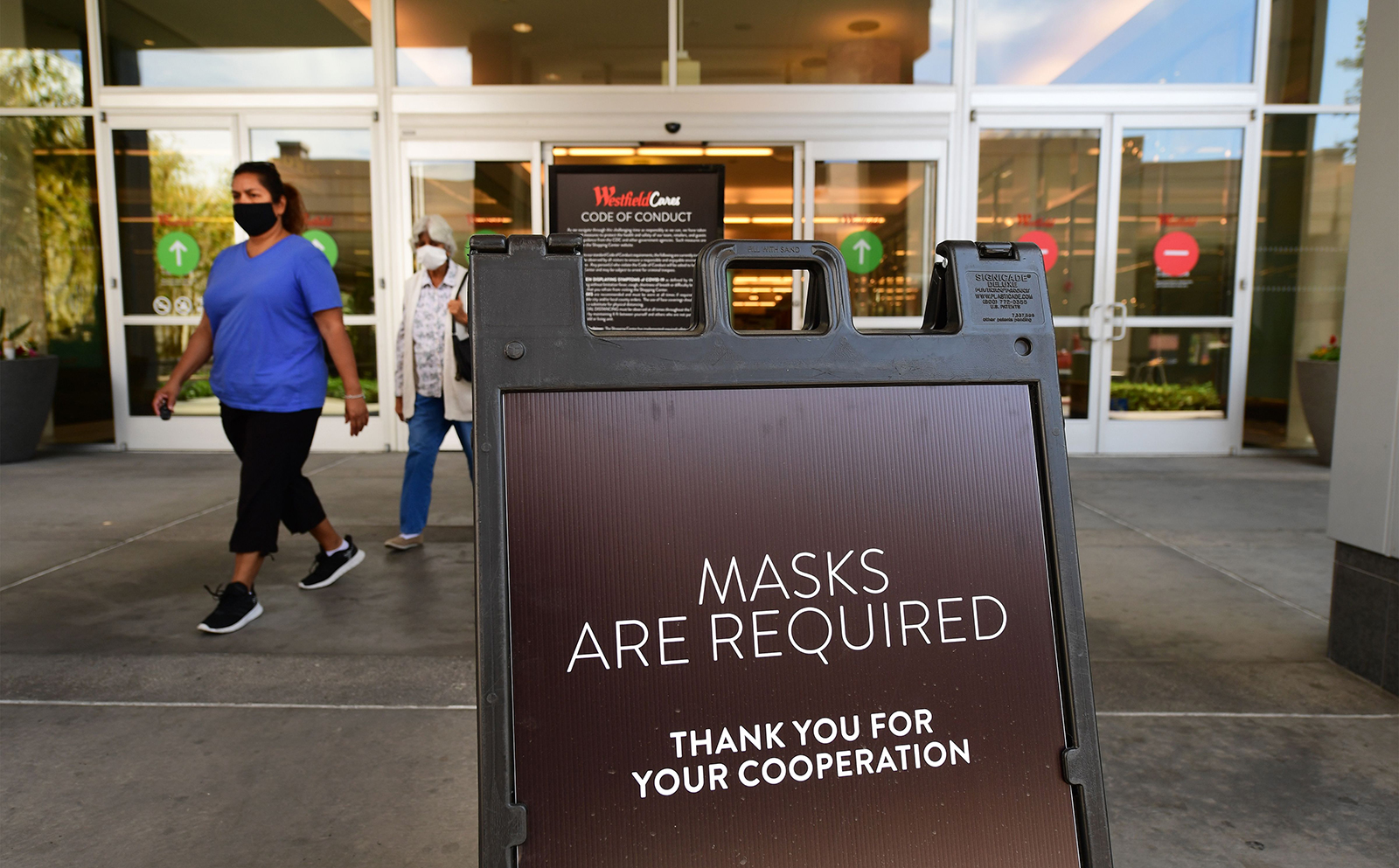 Women wearing face masks exit a shopping mall where a sign is posted at an entrance reminding people of the mask requirement Westfield Santa Anita shopping mall in Arcadia, California, on June 12.