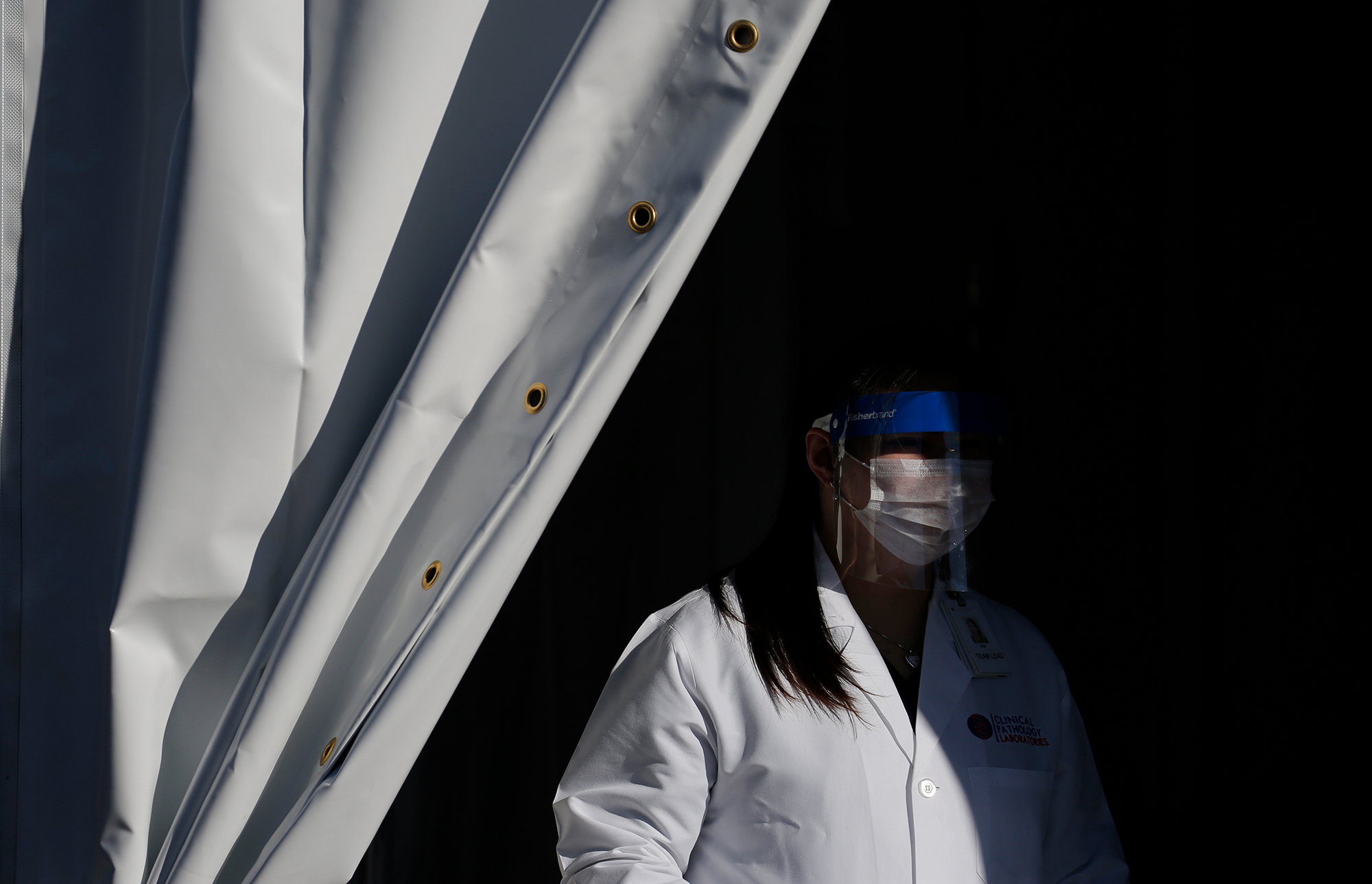 A worker with Clinical Pathology Laboratories waits for patients at a drive-through coronavirus testing site Tuesday, March 24, in Las Vegas.
