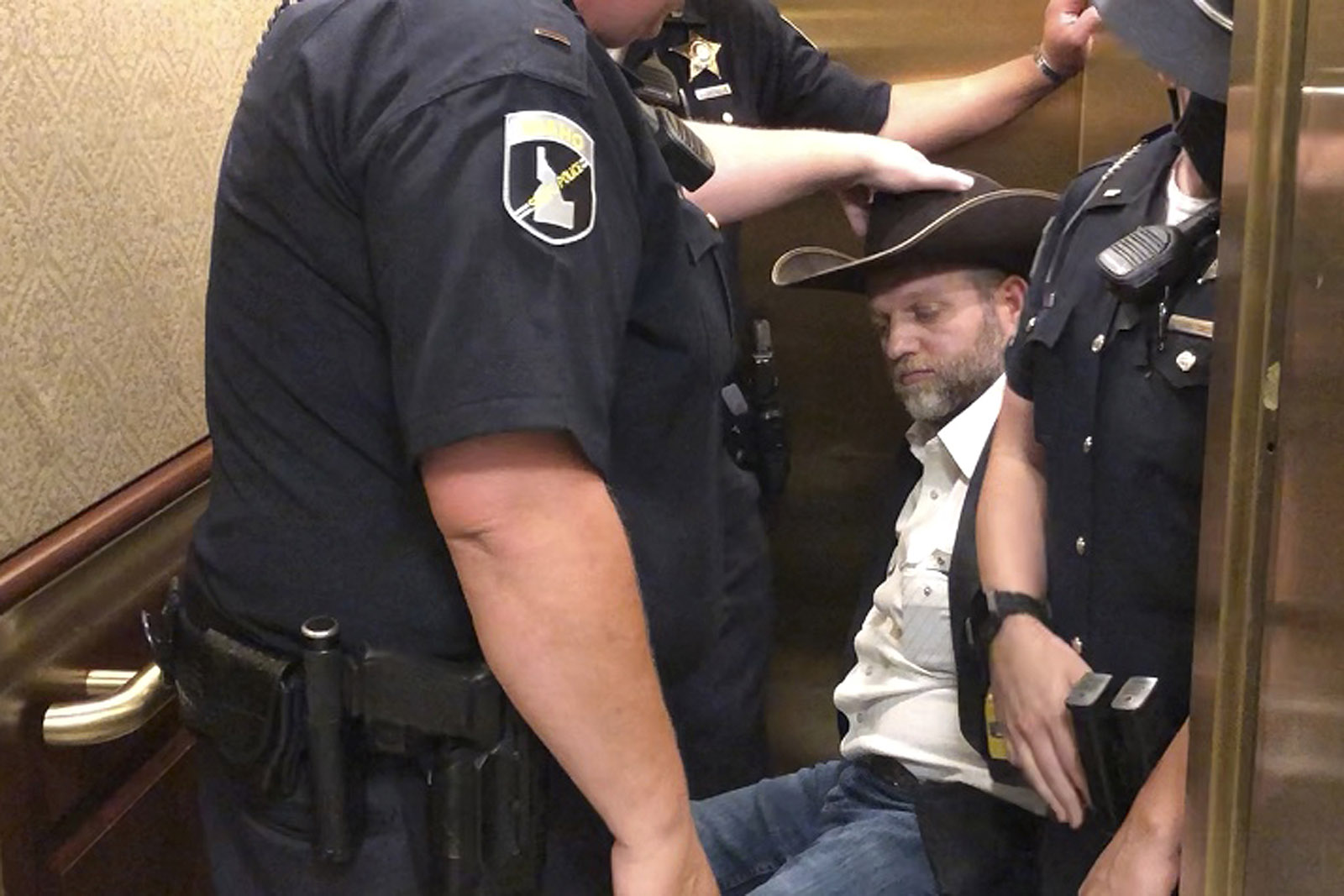 This image taken from video shows anti-government activist Ammon Bundy, rear, being wheeled into an elevator in a chair following his arrest at the Idaho Statehouse in Boise, Idaho, Tuesday, August 25.
