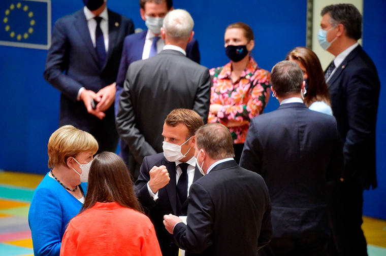 France's President Emmanuel Macron (center) talks with Germany's Chancellor Angela Merkel (left), Finland's Prime Minister Sanna Marin (2nd, left) and Sweden's Prime Minister Stefan Lofven prior the start of the EU summit at the European Council building in Brussels, on July 18, 2020.