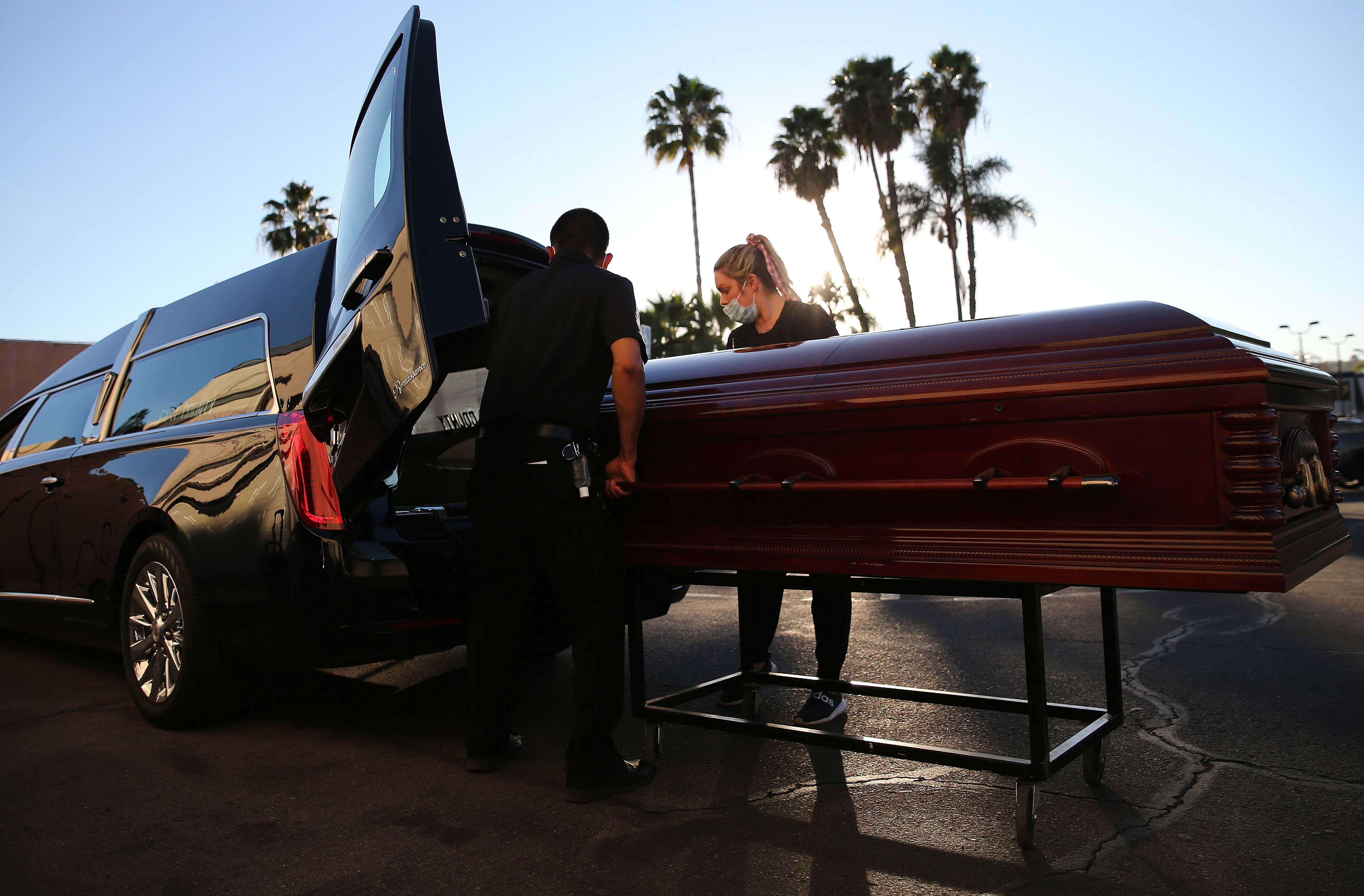 Embalmer and funeral director Kristy Oliver, right, and funeral attendant Sam Deras load the casket of someone said to have died after contracting Covid-19 into a hearse at East County Mortuary in El Cajon, California, on January 15.
