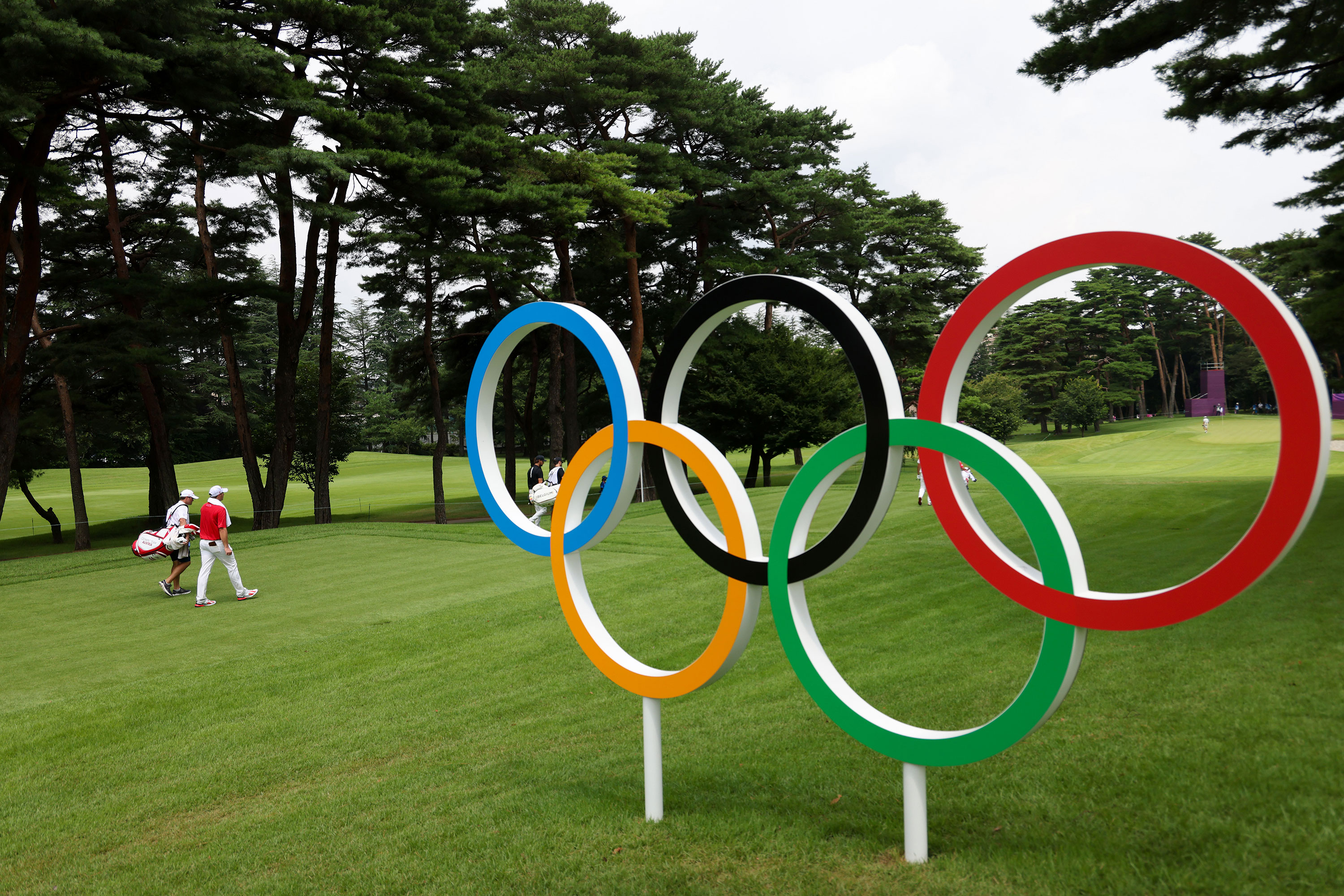 Australia's Sepp Straka and caddie Samuel Straka walk by Olympic rings on the 16th hole during the first round of the individual stroke play in Kawagoe, Japan, on July 29.