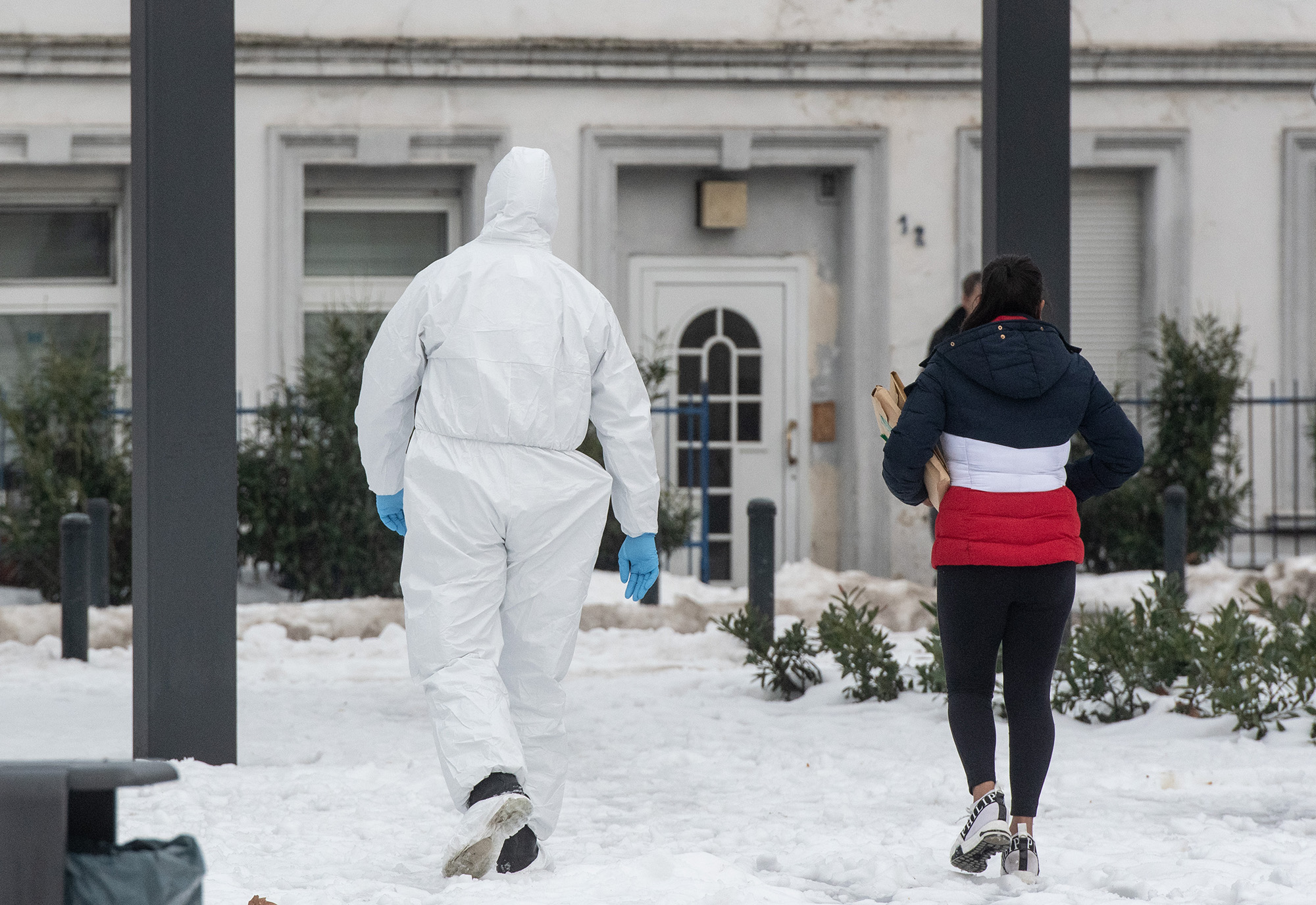 Apolice officer wearing a protective suit escorts a woman to a house in Hamm, Germany on Tuesday.