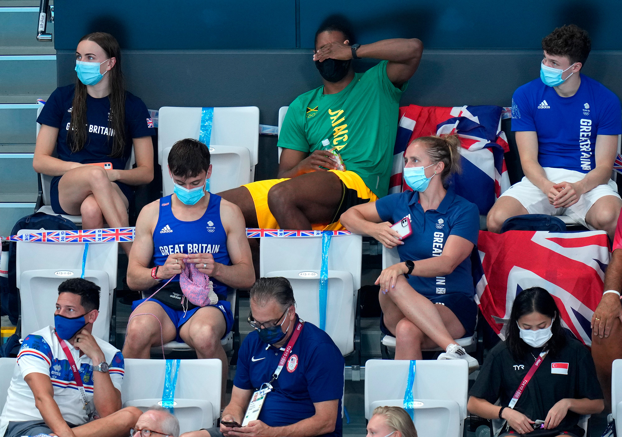"""British diver Tom Daley works on a new creation while watching the women's 3 meter springboard final on Sunday. Daley said on Instagram that he was making a """"jumper,"""" or sweater, for a French bulldog."""